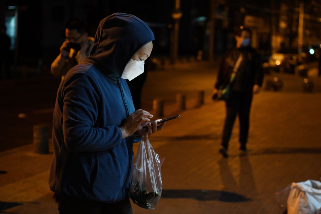 A woman wearing a facemask as a preventive measure against the COVID-19 novel coronavirus prepares to pay 'touchless' with her mobile phone for vegetables at a market in Beijing on March 23, 2020.