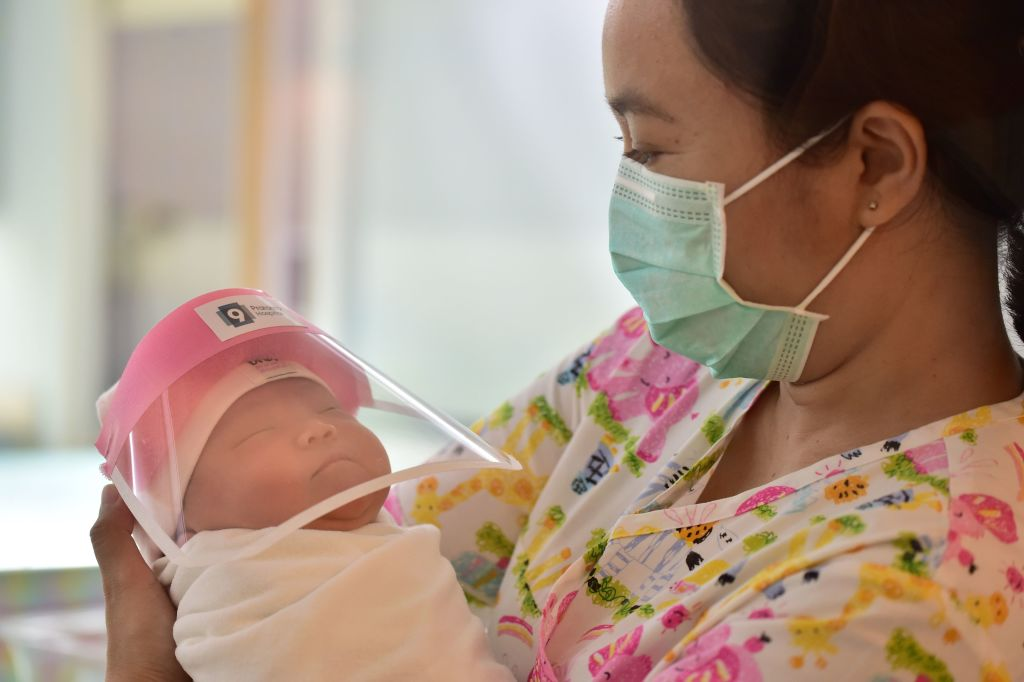 This photo taken through a glass window at a maternity ward shows a nurse holding a newborn baby wearing a face shield, in an effort to halt the spread of the COVID-19 coronavirus, at Praram 9 Hospital in Bangkok on April 9, 2020.