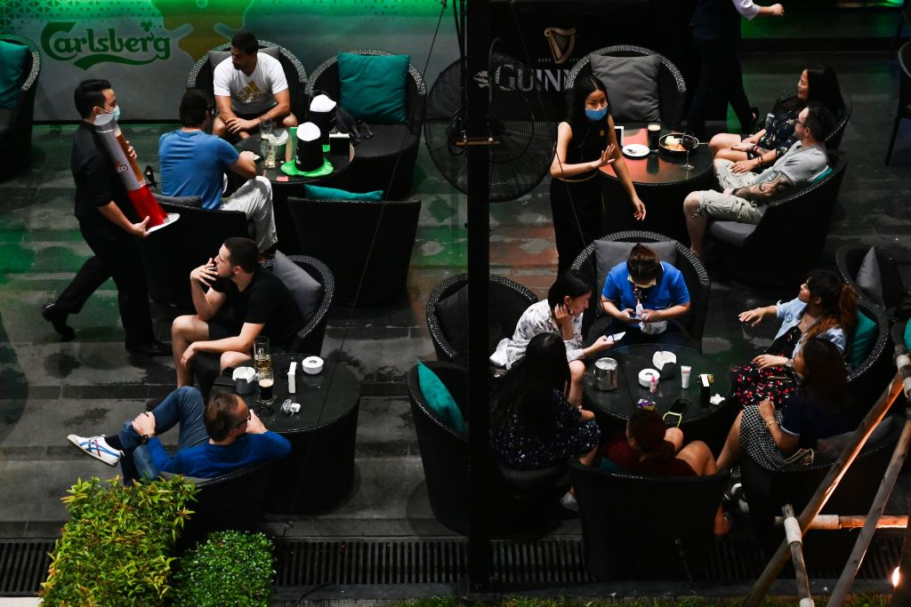 Waiters wearing facemasks as a preventive measure against the spread of the COVID-19 coronavirus serve customers at a hotel bar in Bangkok on March 17, 2020.