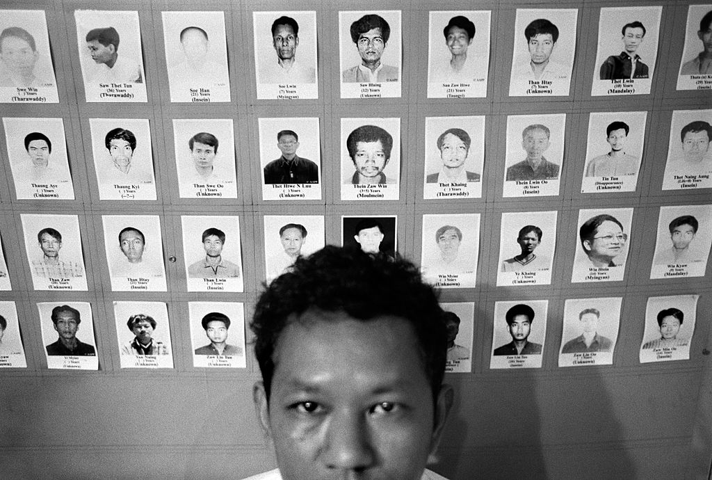 Ko Bo Kyi poses with photographs of Myanmar political prisoners in Thailand on Oct. 10, 2007.