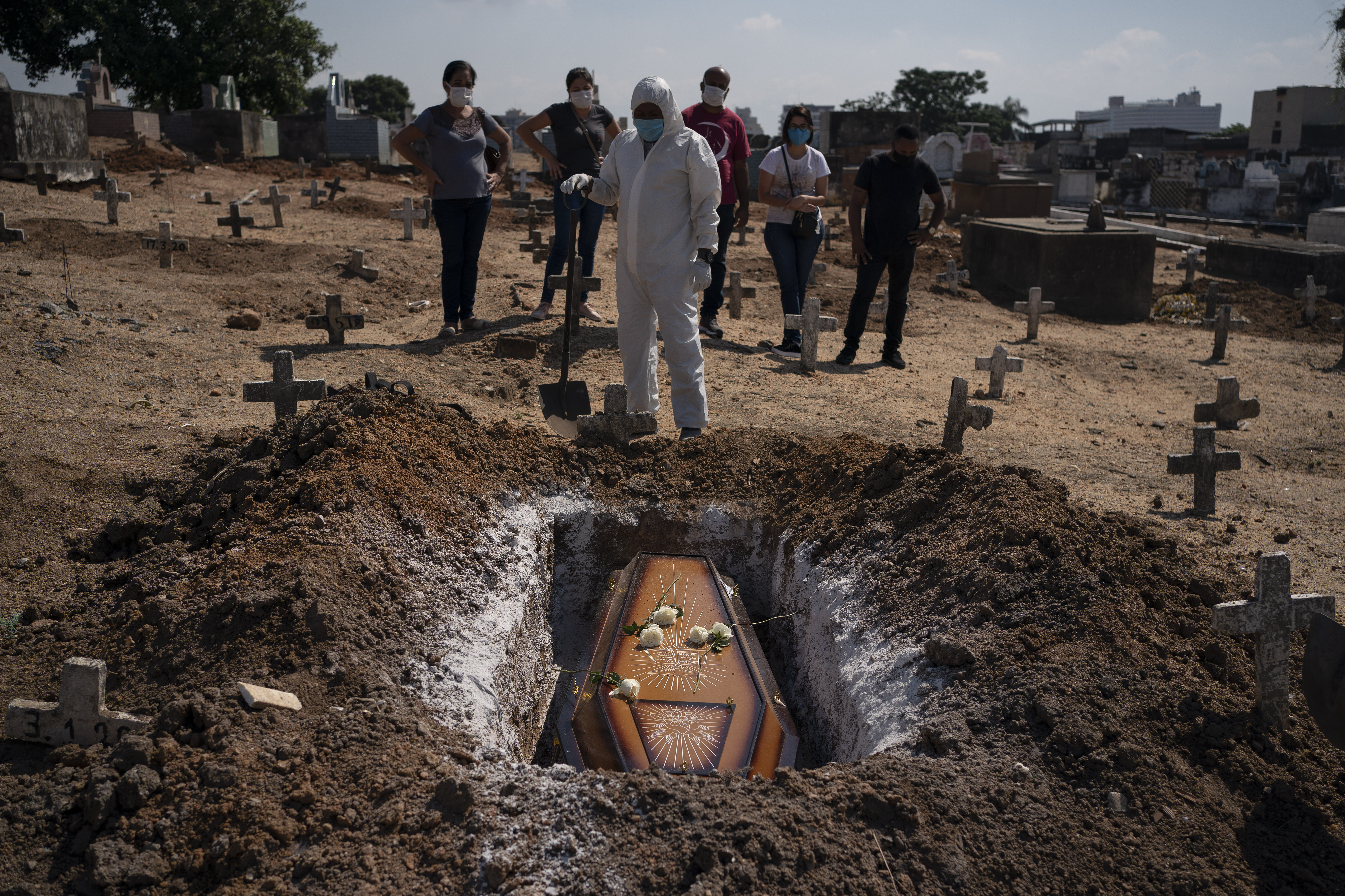 A cemetery worker stands before the coffin containing the remains of Edenir Rezende Bessa as relatives attend her burial in Rio de Janeiro on April 22, 2020.