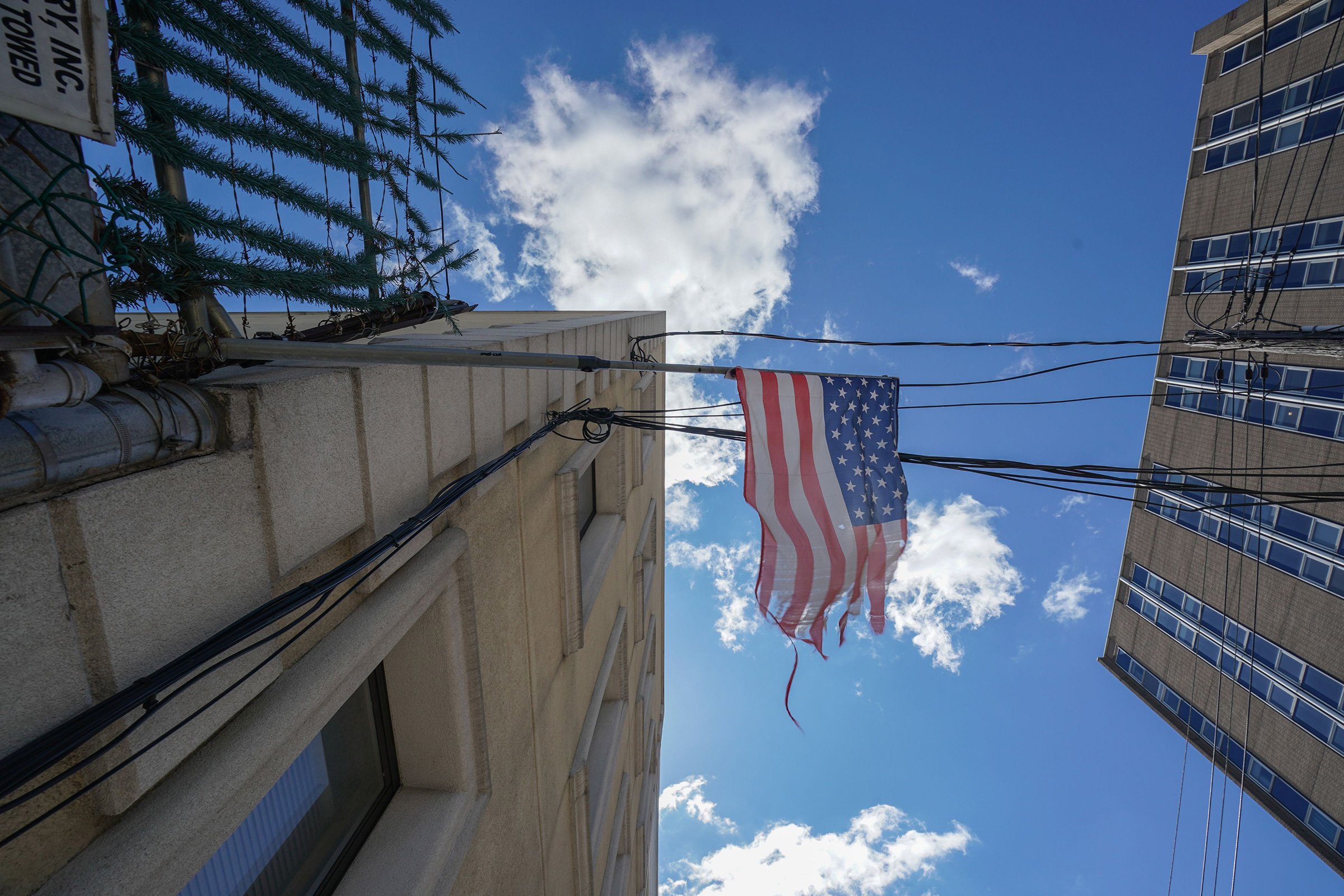 A tattered American flag hangs from a fence across the street from Wyckoff Hospital in Brooklyn, N.Y. on April 4, 2020.
