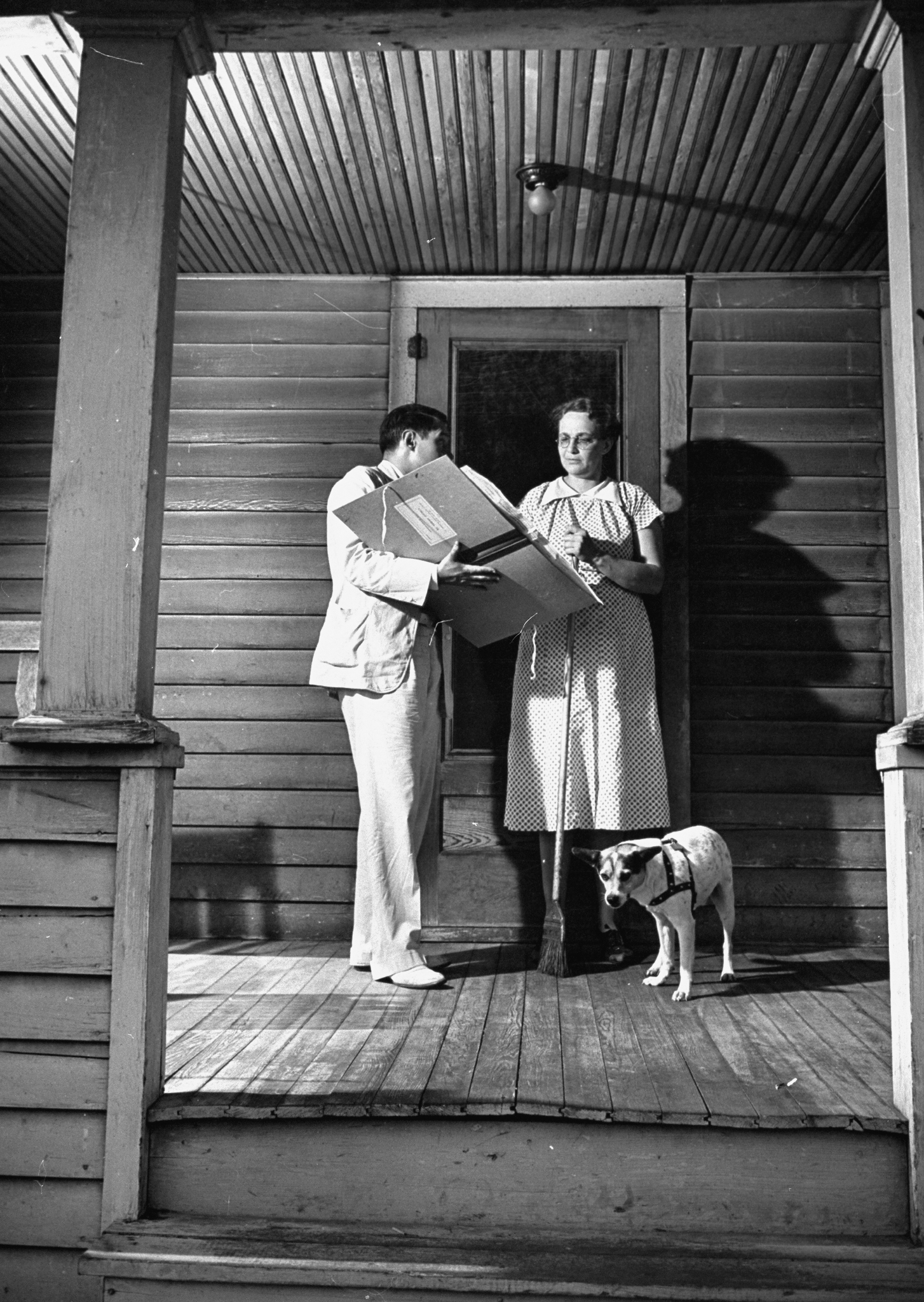Census taker talking with a housewife on porch of her home, c. 1940.