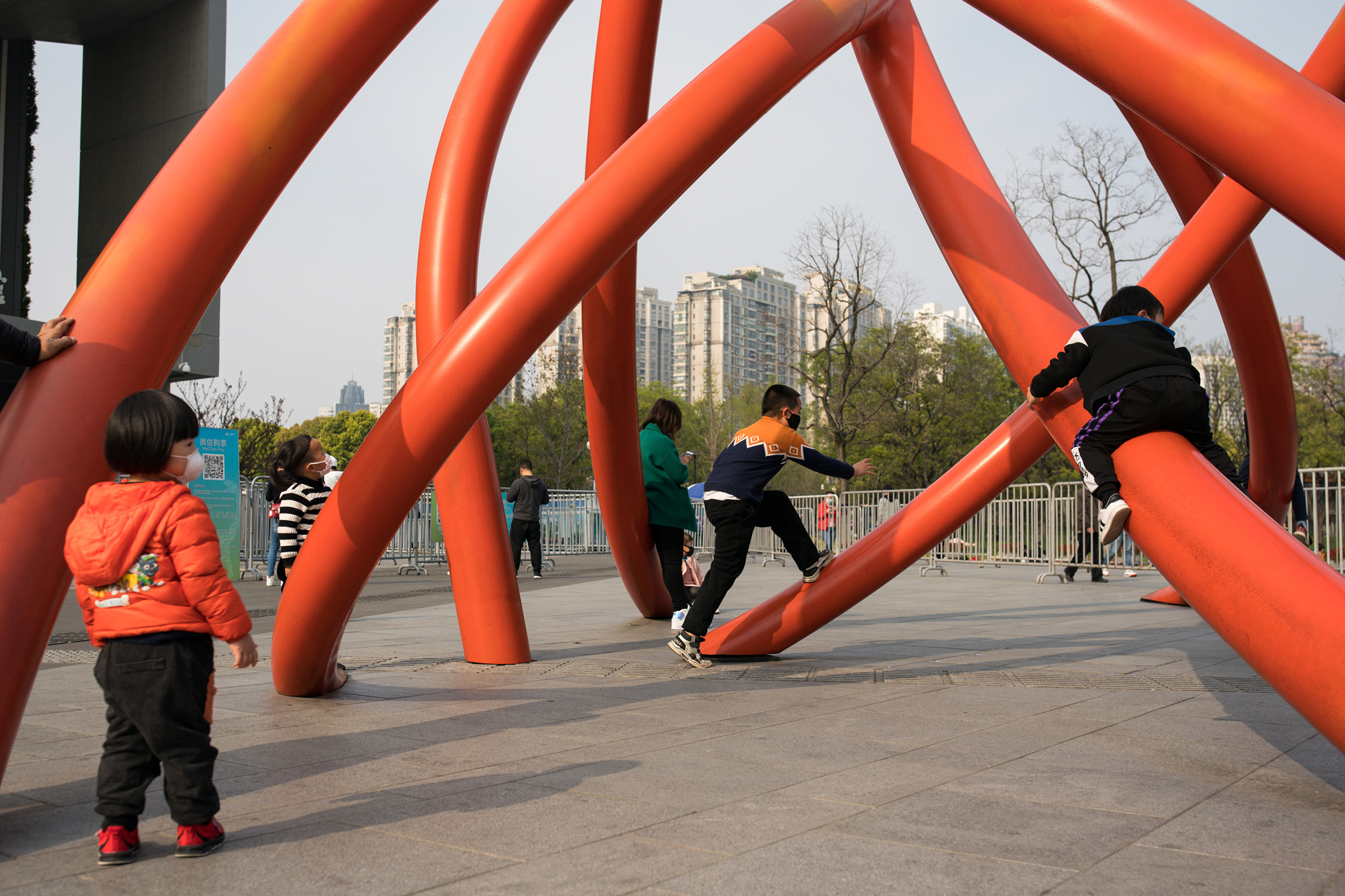 Children wear protective masks while playing under a sculpture in a city park on April 01, in Shanghai, China