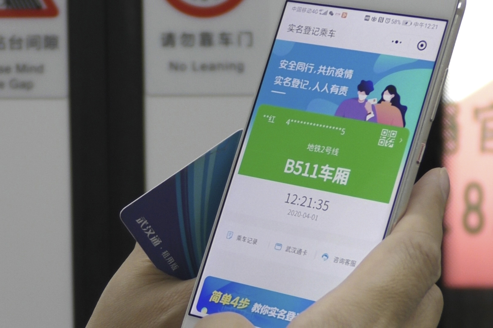 In this April 1, 2020, photo, a passenger holds up a green pass on their phone on a subway train in Wuhan in central China's Hubei province.