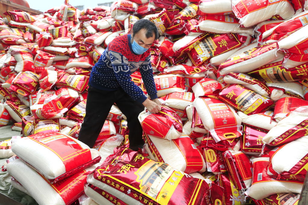 SUINING, CHINA - FEBRUARY 18 2020: A masked laborer moves bags of rice off a truck in Suining city in southwest China's Sichuan province Tuesday, Feb. 18, 2020.