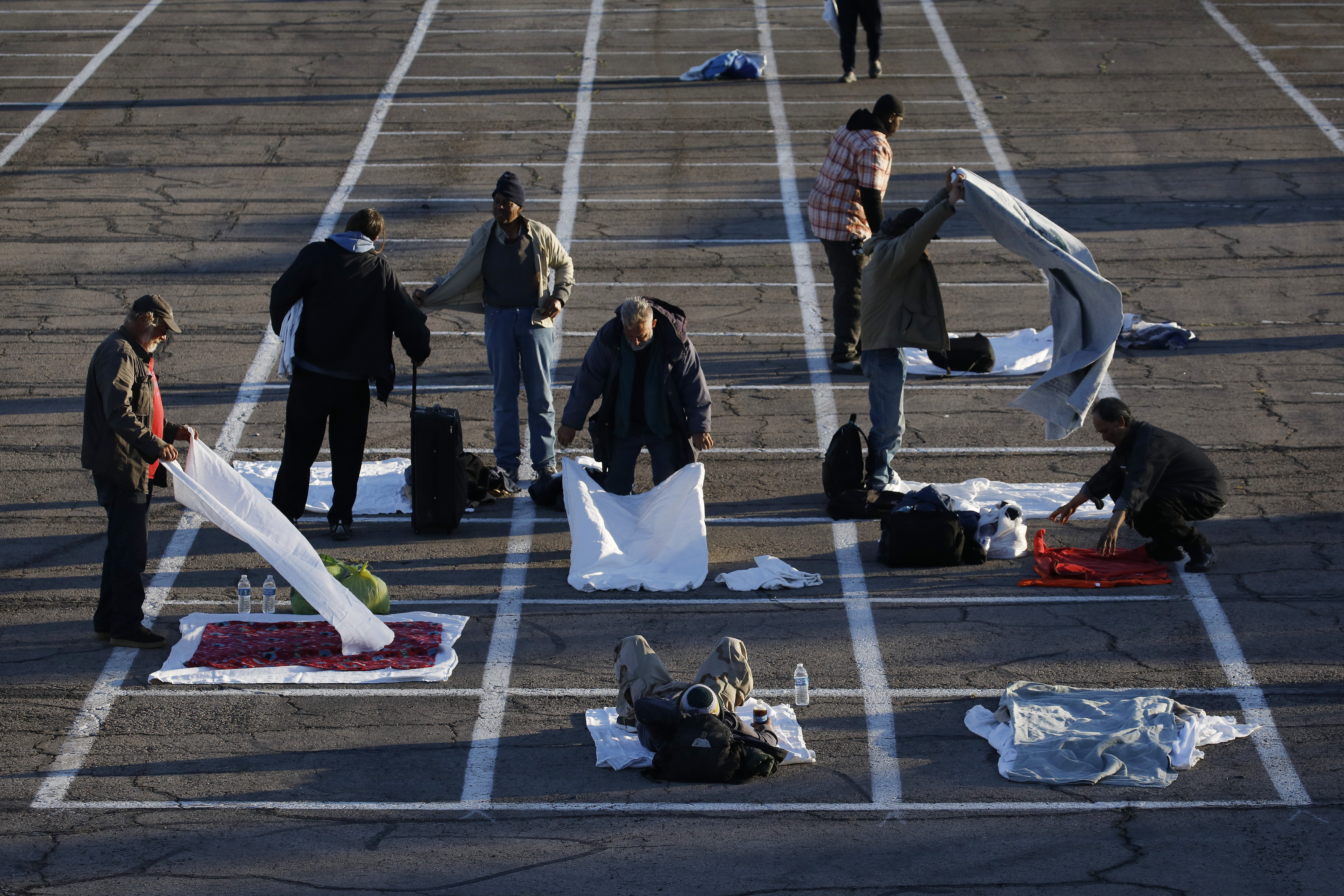 People prepare places to sleep in area marked by painted boxes on the ground of a parking lot at a makeshift camp for the homeless on March 30, 2020, in Las Vegas.