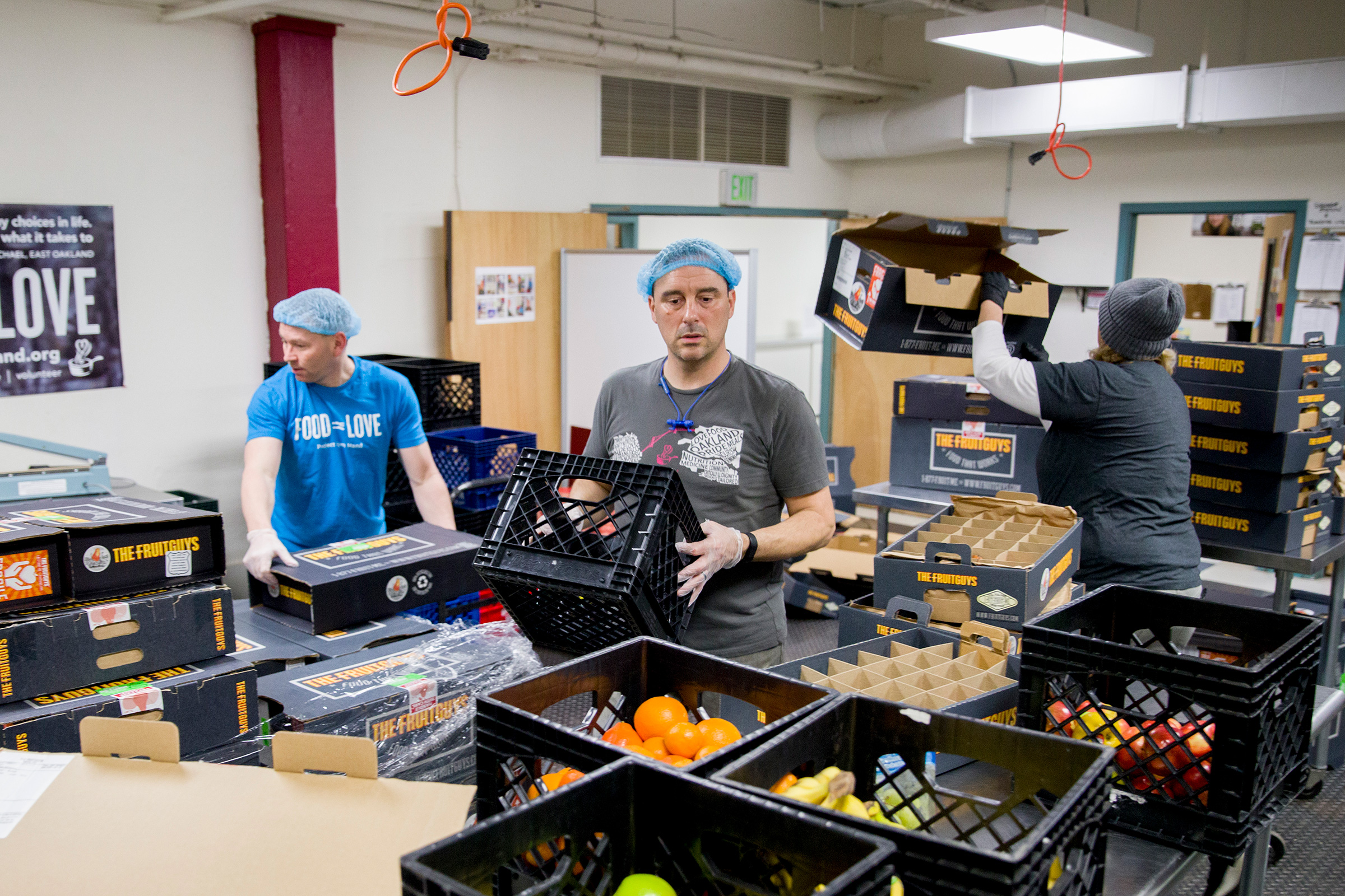 Michael McCormick and Daniel Cohen, of Project Open Hand, and Cindy Neill, operations manager for The Fruit Guys,                 sort through a palette of donated fruit boxes in the volunteer space at Project Open Hand in San Francisco, Calif. on March 25, 2020.