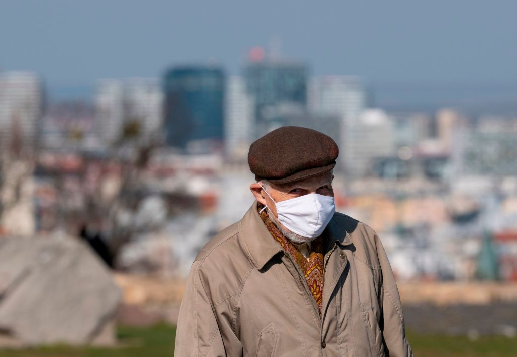 An elderly man wears a face mask to prevent the spread of the new coronavirus that can cause the COVID-19 disease as he walks in front of the Bratislava castle in Bratislava, Slovakia on April 1, 2020.