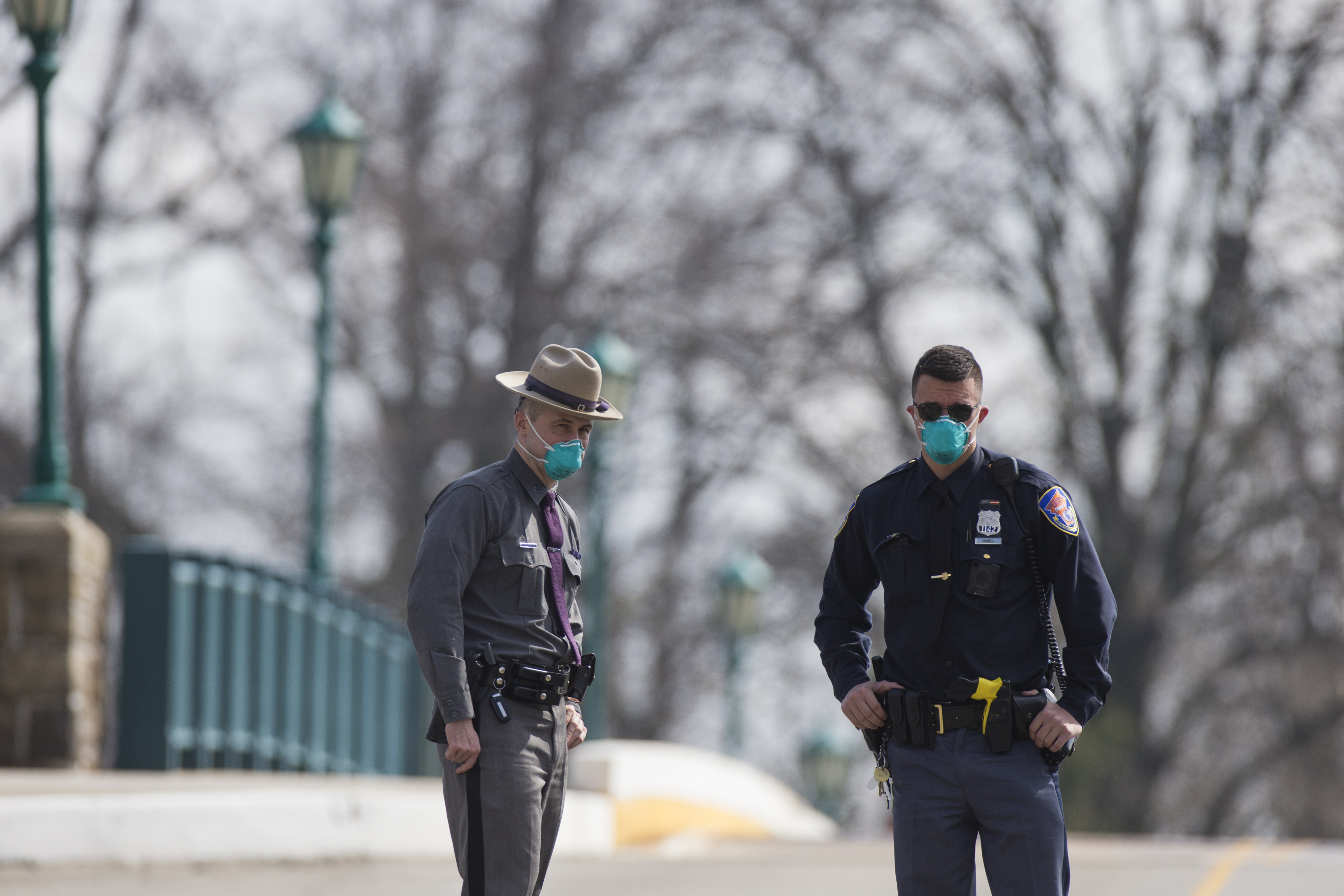 Police officers wear protective masks while maintaining a road block on the bridge leading to a  drive-through testing facility at Glen Island Park in New Rochelle, New York, on March 13, 2020.