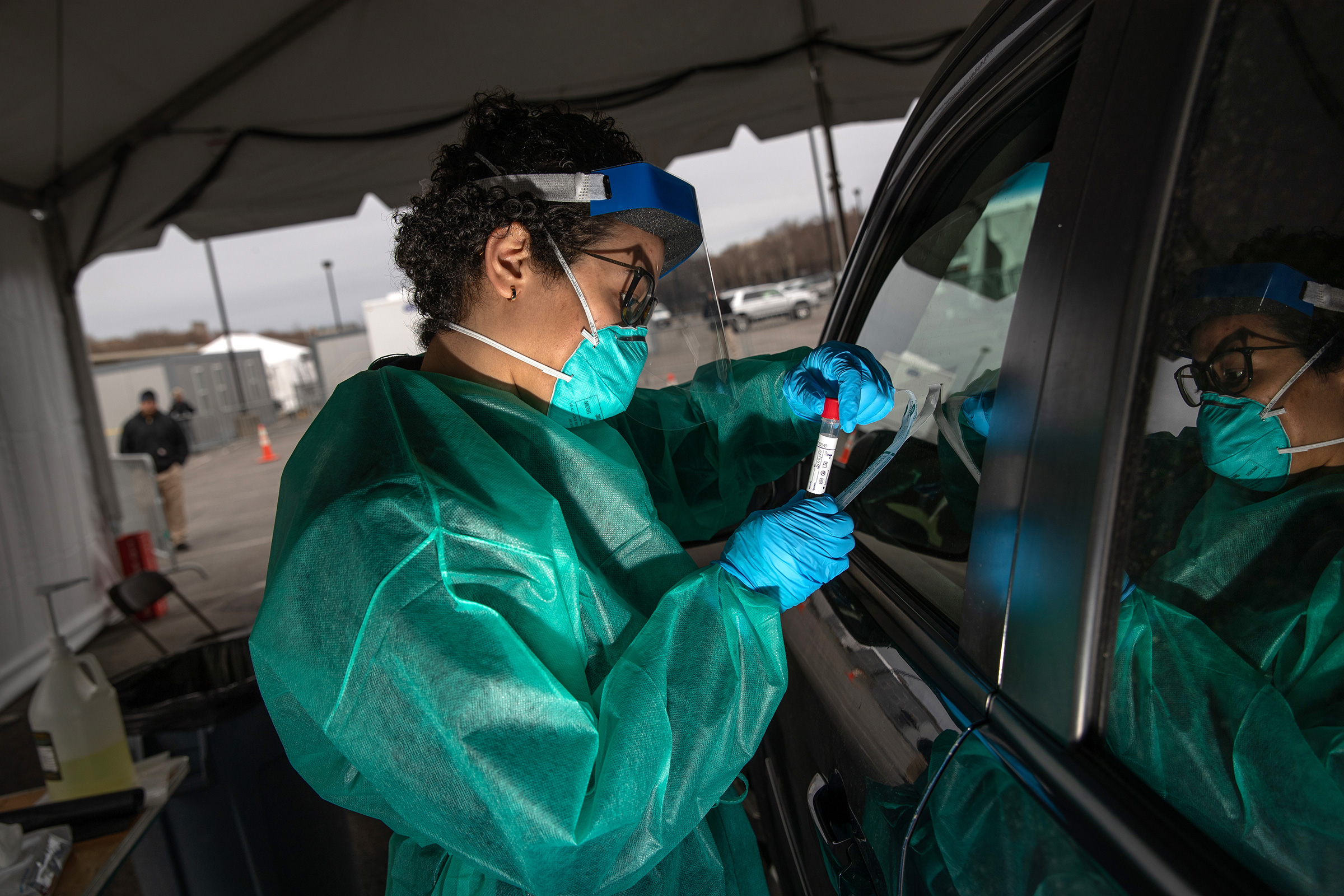 A health worker handles a coronavirus swab test at a drive-thru testing center for COVID-19 at Lehman College on in the Bronx, N.Y., March 28, 2020.