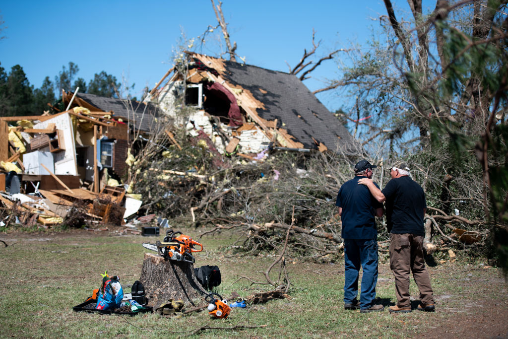 Two men talk in front of a home destroyed by a tornado on April 13, 2020 near Nixville, South Carolina.
