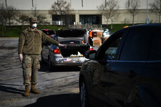 A soldier directs traffic during a drive-thru food distribution event at Wright State University's Nutter Center in Fairborn, Ohio, on April 21, 2020.