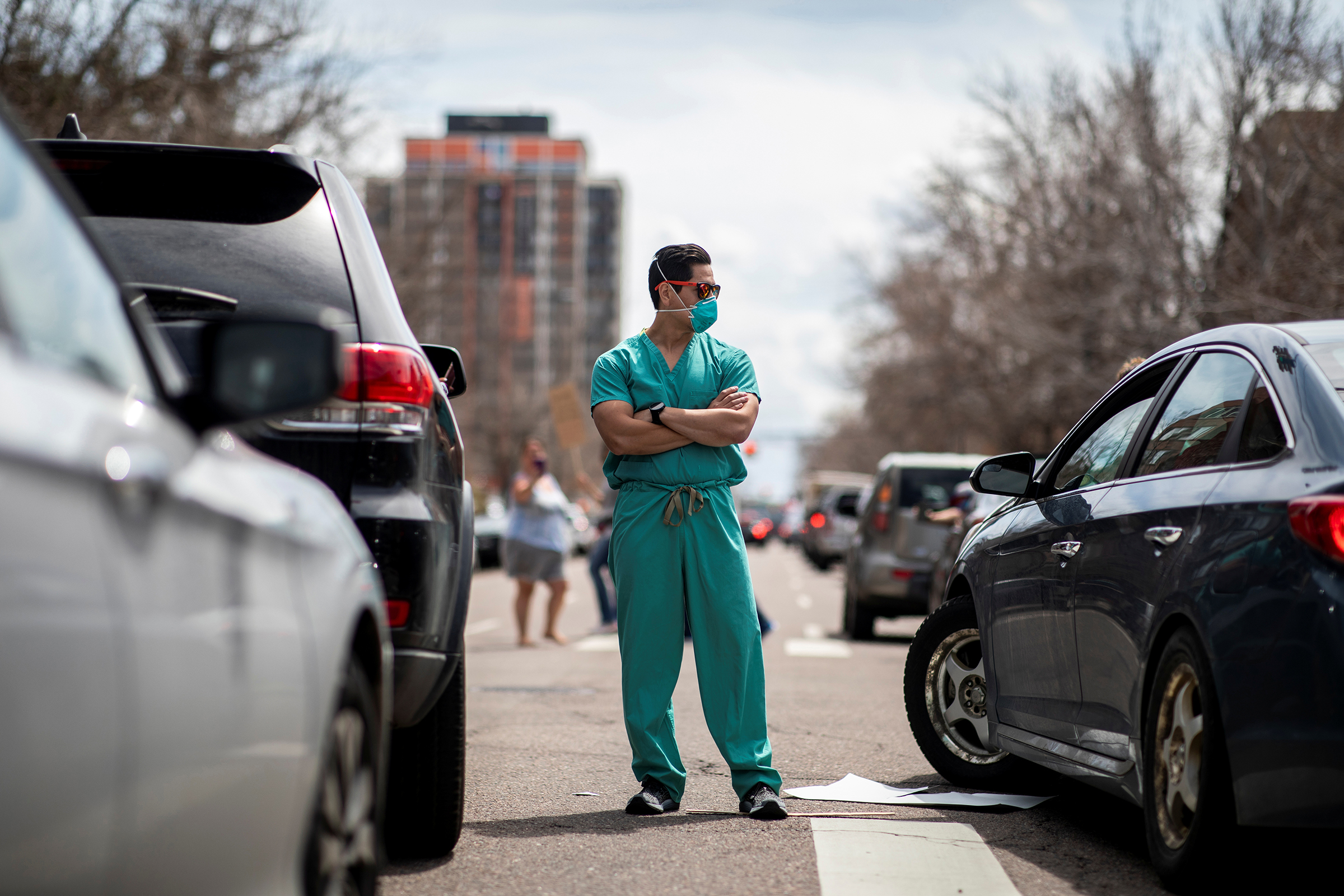 A health care worker blocks the street to counter-protest the hundreds of people who gathered at the State Capitol to demand the stay-at-home order be lifted in Denver, Colorado, on April 19, 2020.