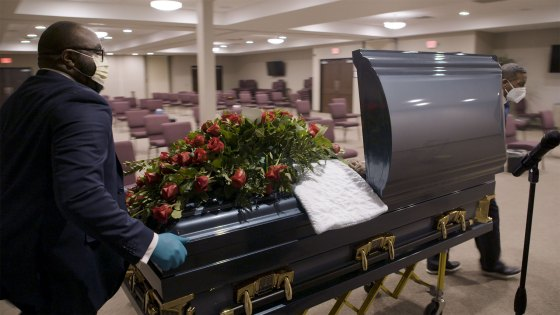 A man pushes a casket inside a Detroit funeral home