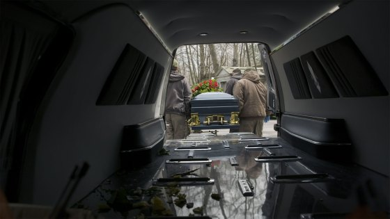 A casket is taken out of the back of a hearse at a cemetery