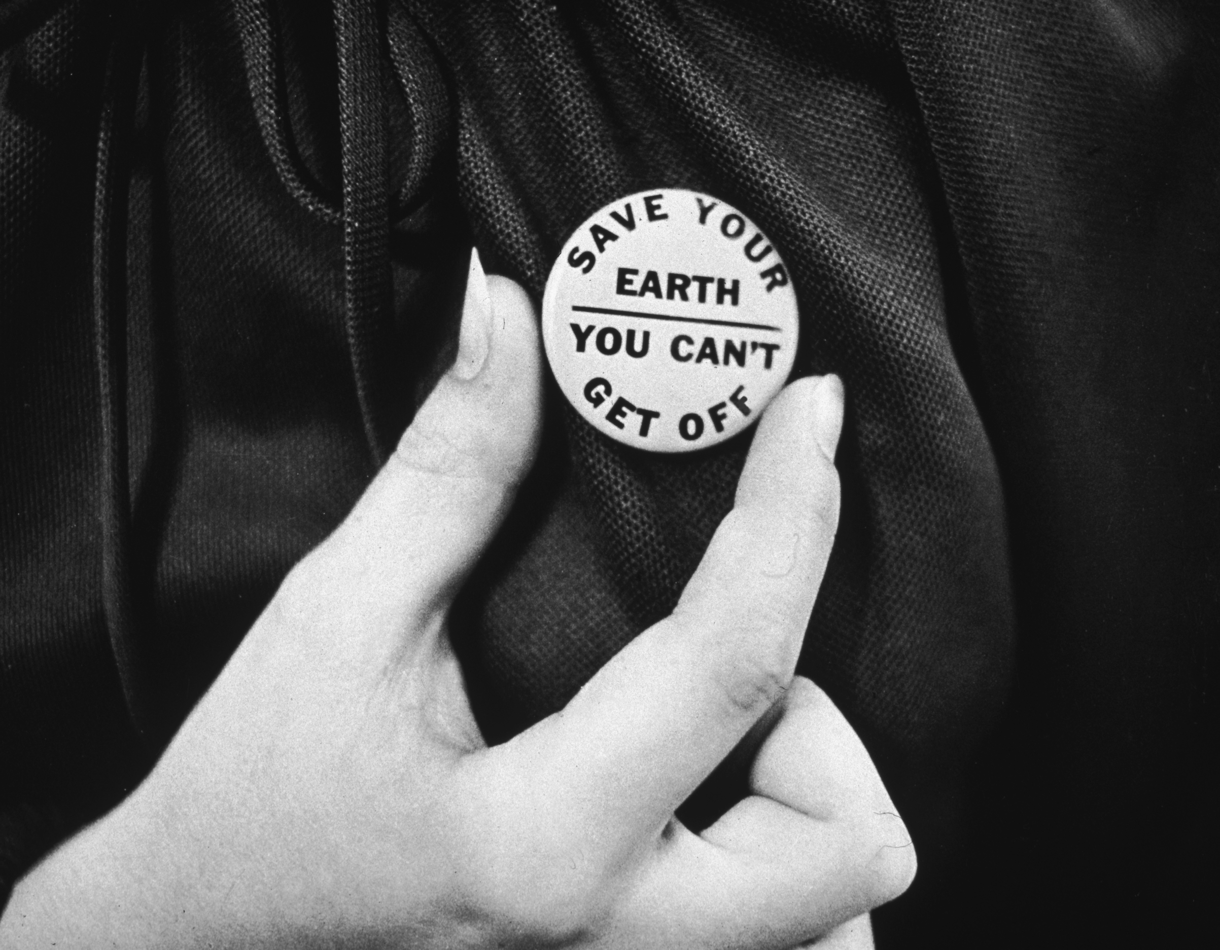 circa 1970:  A close-up of a hand holding up an Earth Day button.