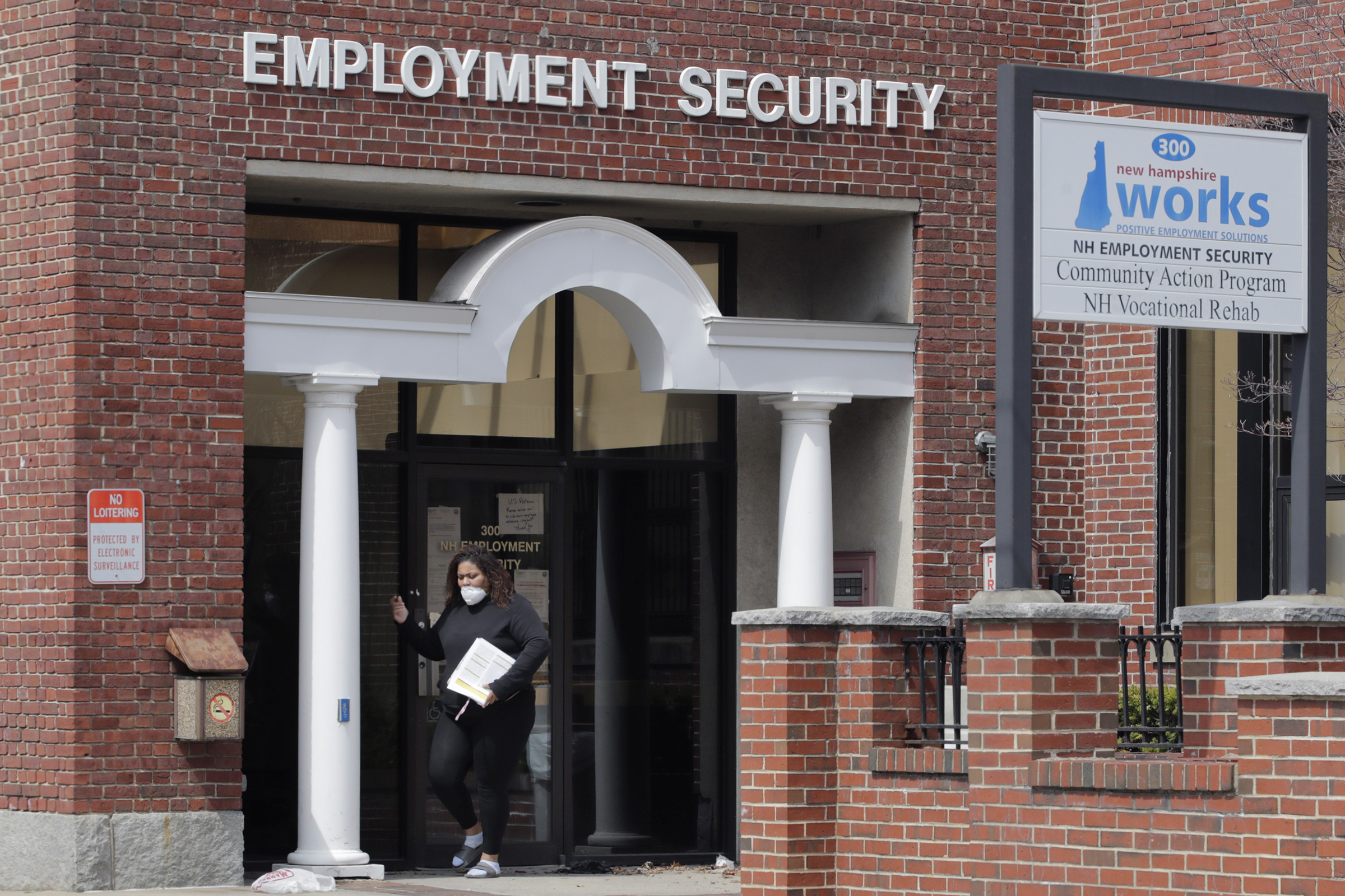 A woman walks away from a locked door at the New Hampshire Employee Security center, which handles unemployment claims, in Manchester, N.H., on April 16, 2020.