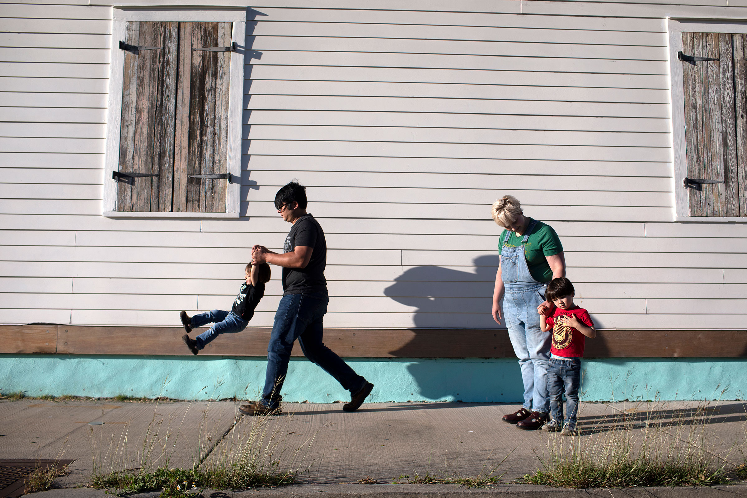 Mickey Harrison and his wife Laurie Halbrook take their kids eighteen month old Jack, left, and Michael, 3, on a walk through their neighborhood in New Orleans.