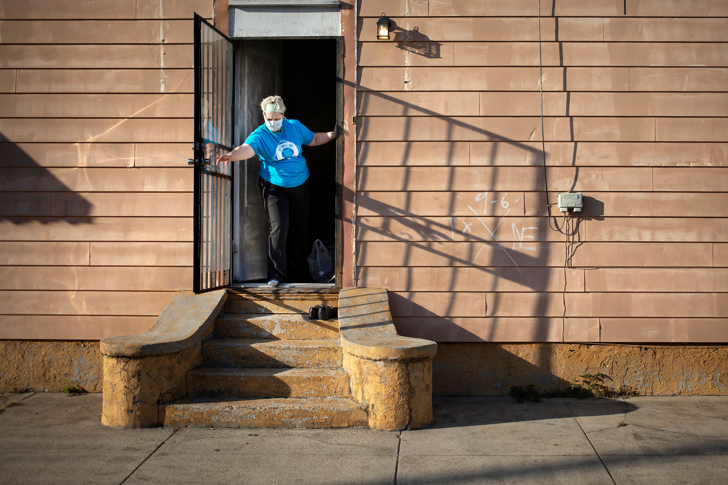 Laurie Halbrook leaves her shoes outside and closes the side door at her house after a shift working as a nurse on April 3, 2020.