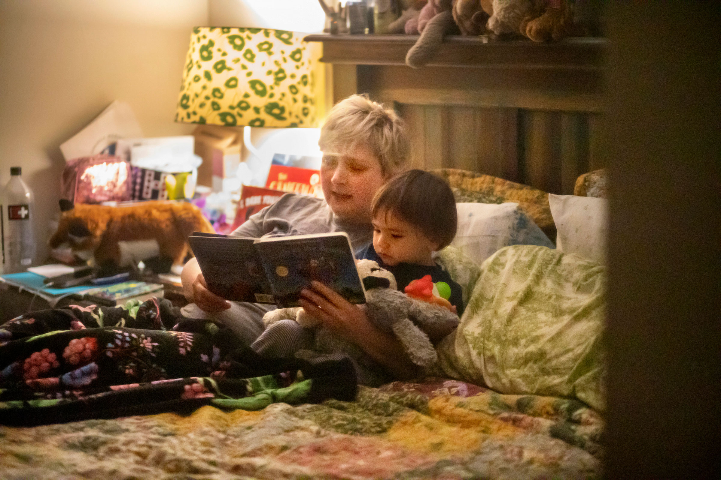 Laurie Halbrook is seen through a window reading a bedtime book to her eighteen month old son Jack, at their home in New Orleans.