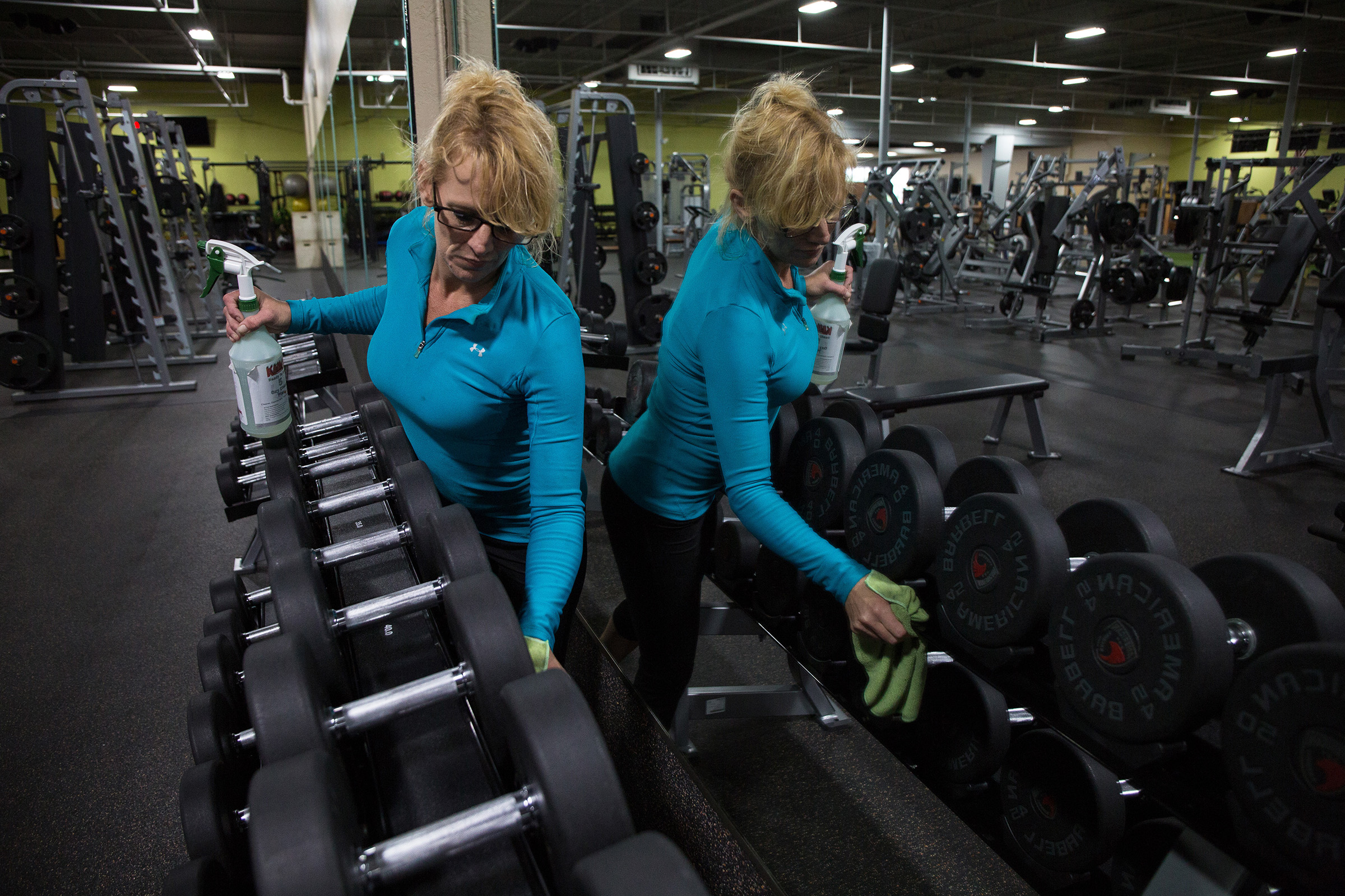 A Gold's Gym worker cleans before reopening, in Evans, Ga., on April 23, 2020.
