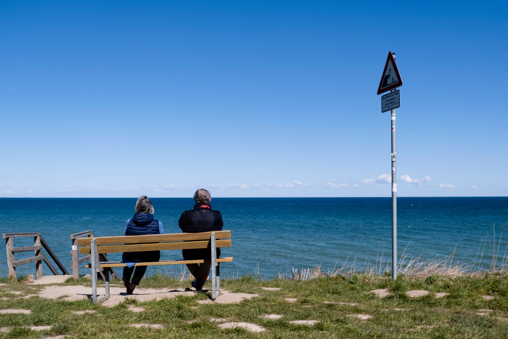 Two people sit on a bench at the Stohler Steep Coast and look out over the Baltic Sea.