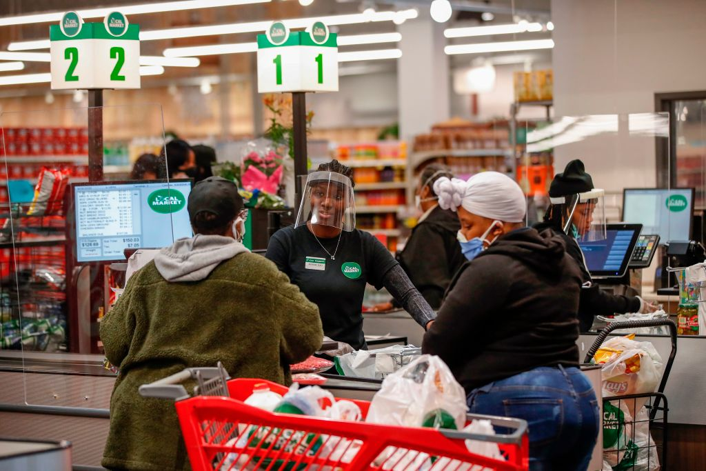 A cashier wearing a face shield talks with a customer as she pays for her groceries at the Local Market Foods store in Chicago, Illinois, on April 8, 2020.