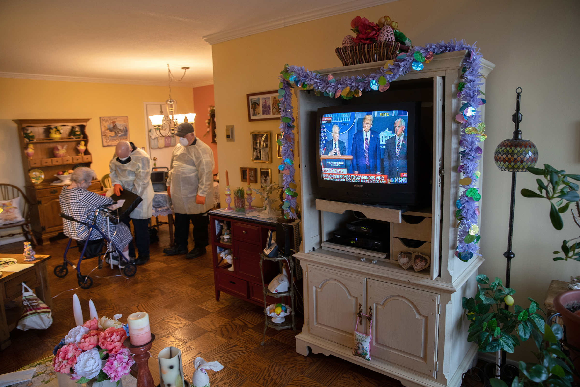 EMS medics wearing personal protective equipment check a woman in her apartment for COVID-19 symptoms during a televised Presidential press conference on April 02 in Stamford, Connecticut.