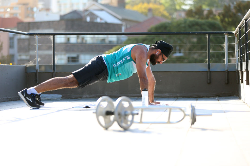 Karam Singh, a Malaysian born financial planner now living in Sydney, participates in a F45 HIIT virtual workout delivered via Zoom on on his Darlinghurst apartment rooftop  on March 28, 2020 in Sydney, Australia.