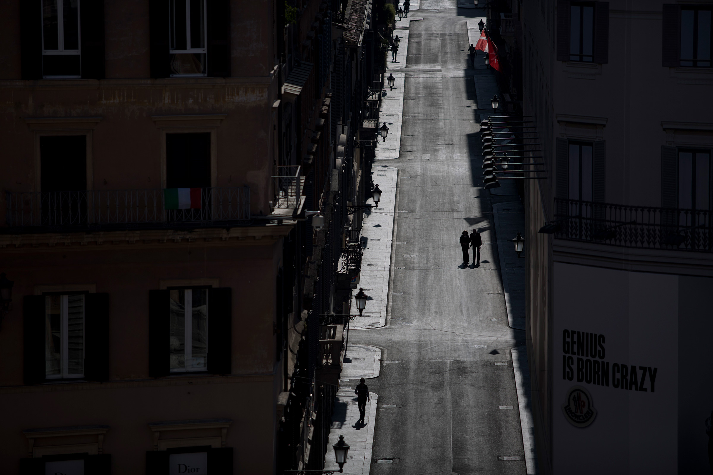 A couple walks in deserted via Condotti in central Rome on April 6, 2020.