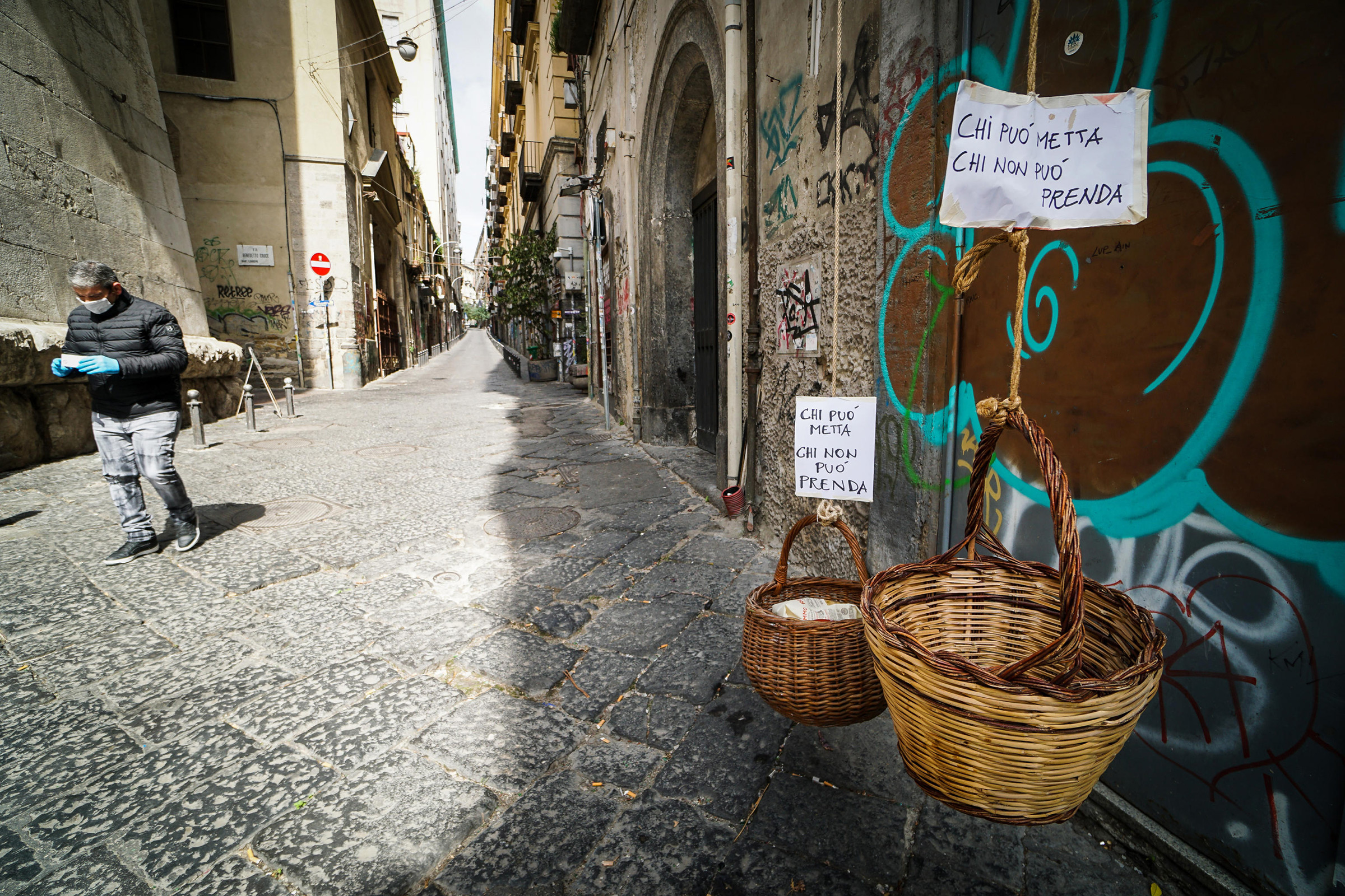 Solidarity baskets with notes reading 'Who can may put, who cannot may take' in one of the deserted streets in the historic center of Naples, southern Italy, on March 30, 2020.