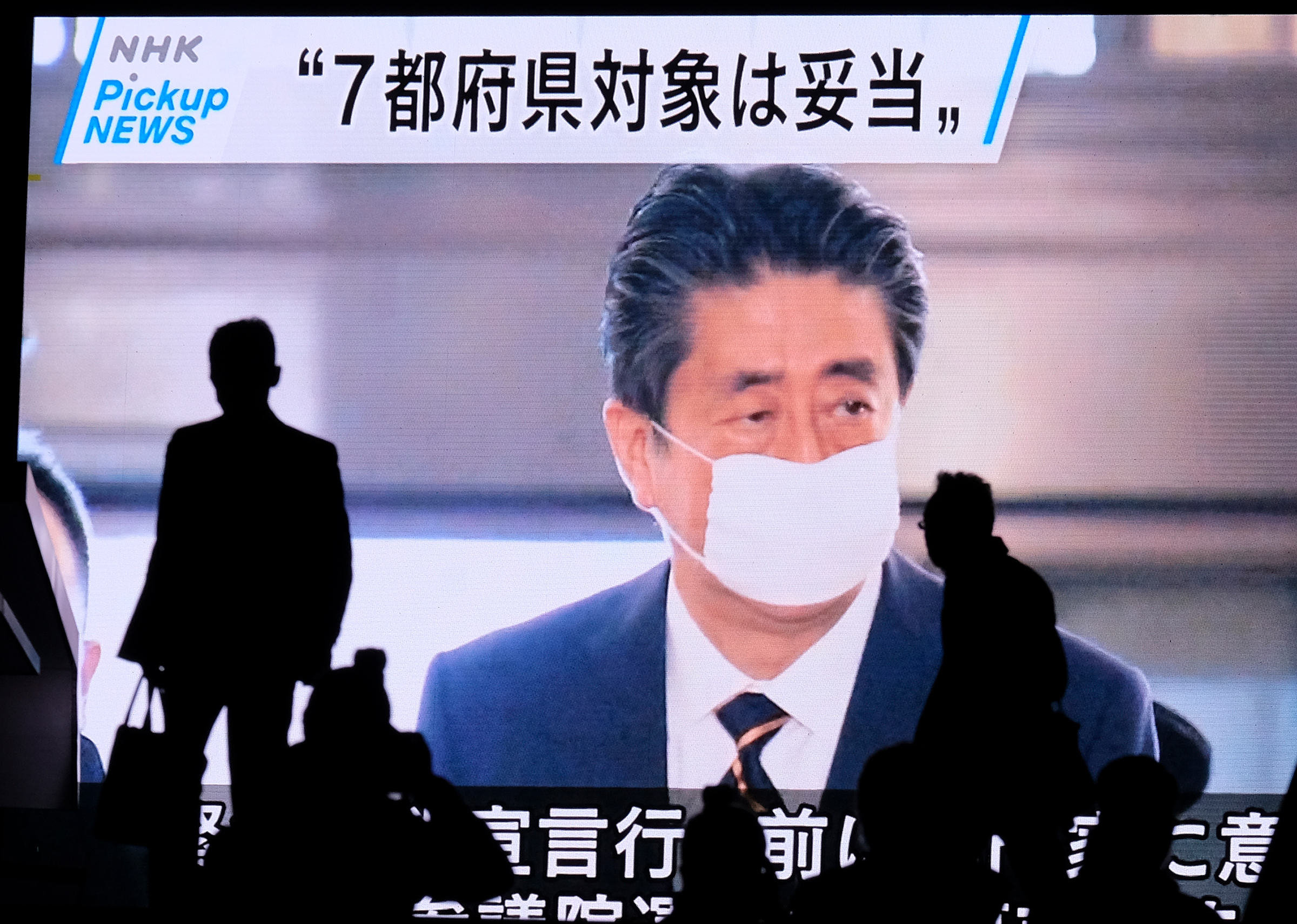 A screen displays news footage of Japan's Prime Minister Shinzo Abe at parliament in Tokyo on April 7