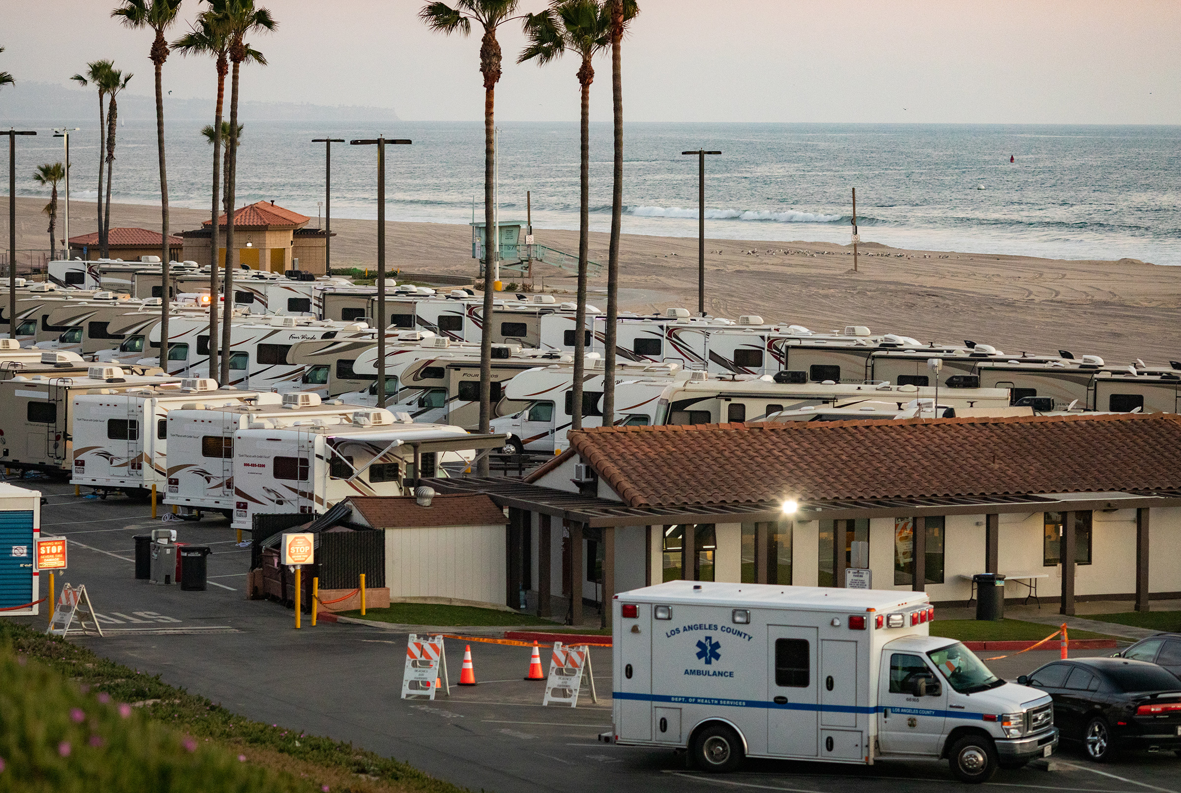 An ambulance arrives in a beachside parking lot being used with R.V's as an isolation zone for people with COVID-19, on April 1st at Dockweiler State Beach in Los Angeles, California