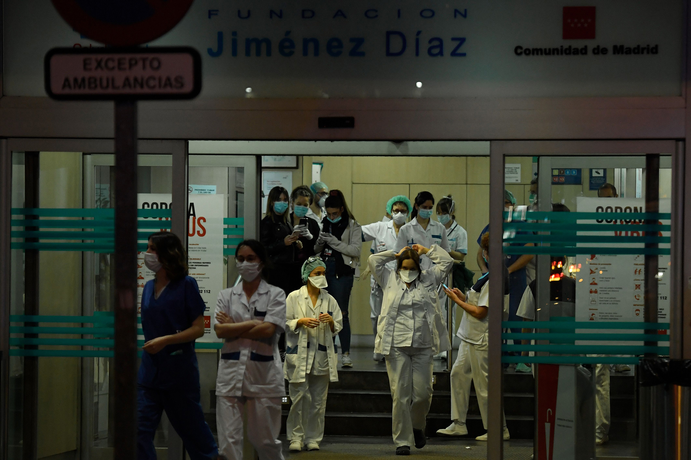 Healthcare workers dealing with the new coronavirus crisis stand at the entrance of the Fundacion Jimenez Diaz hospital in Madrid on March 25