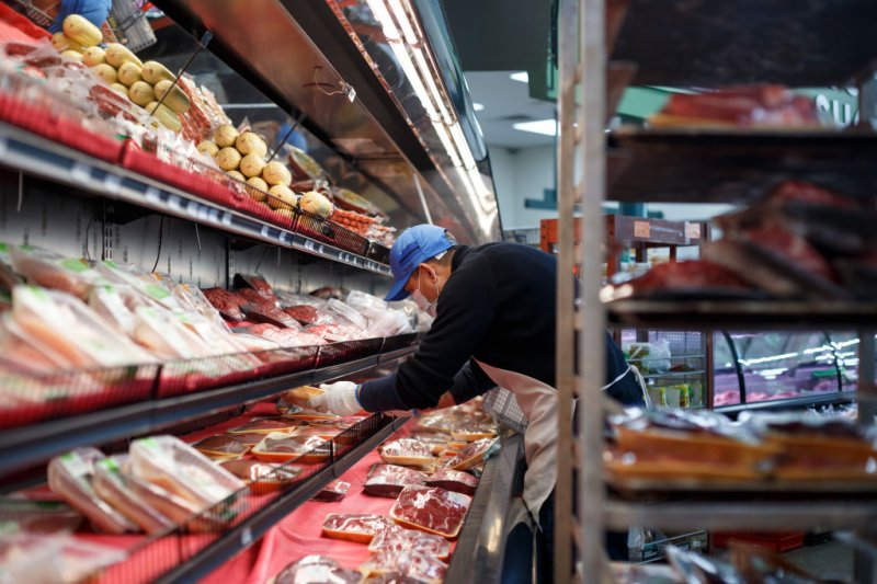 Wearing a mask, an employee stocks the meat section at Greenland Market on April 23, 2020 in Dearborn Heights, Michigan.