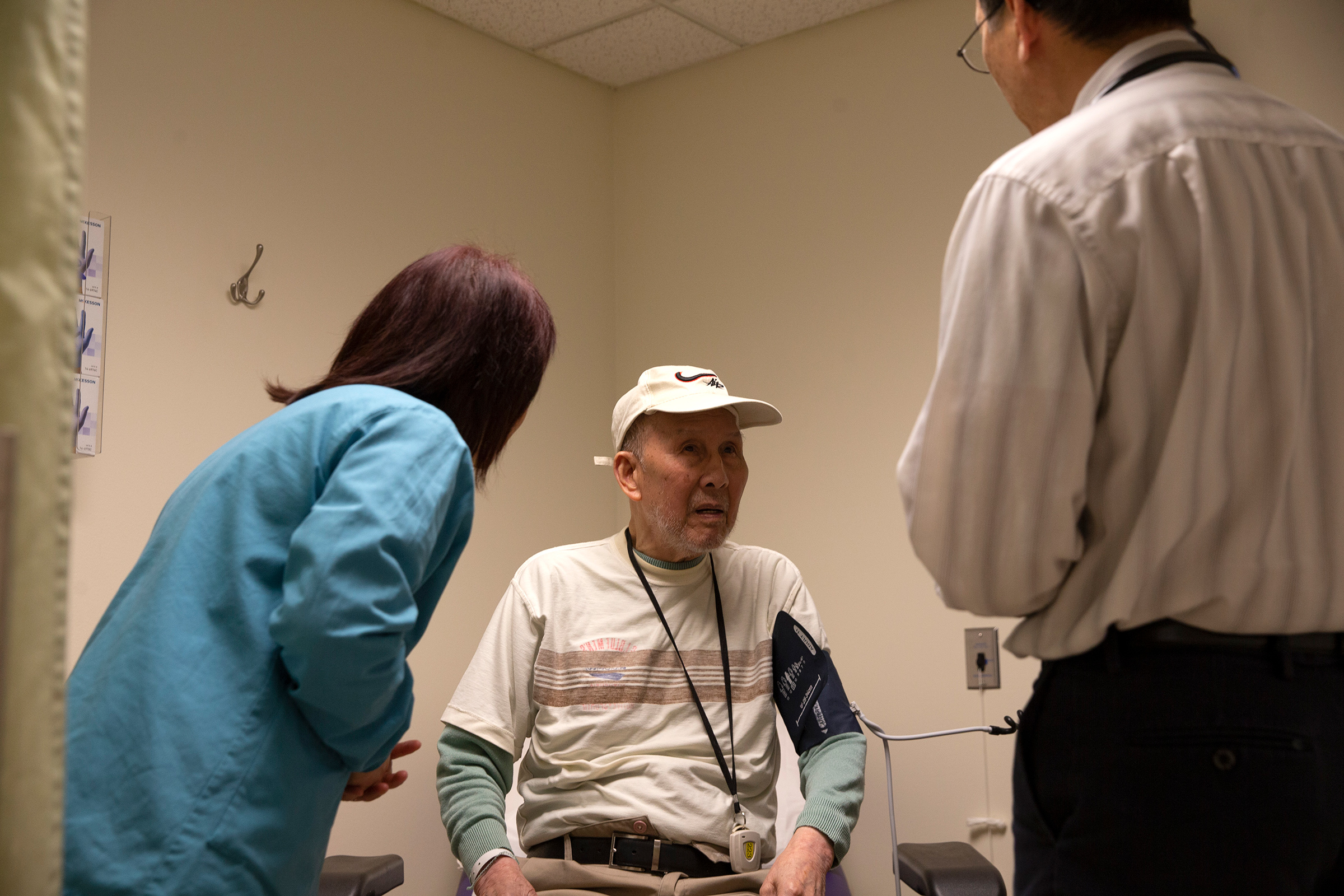 Bing Hong Liu (C) talks to to Dr. Alan Chun (R) through an interpreter at the International Community Health Services medical clinic in their assisted living facility, the Legacy House, on March 20 in Seattle.