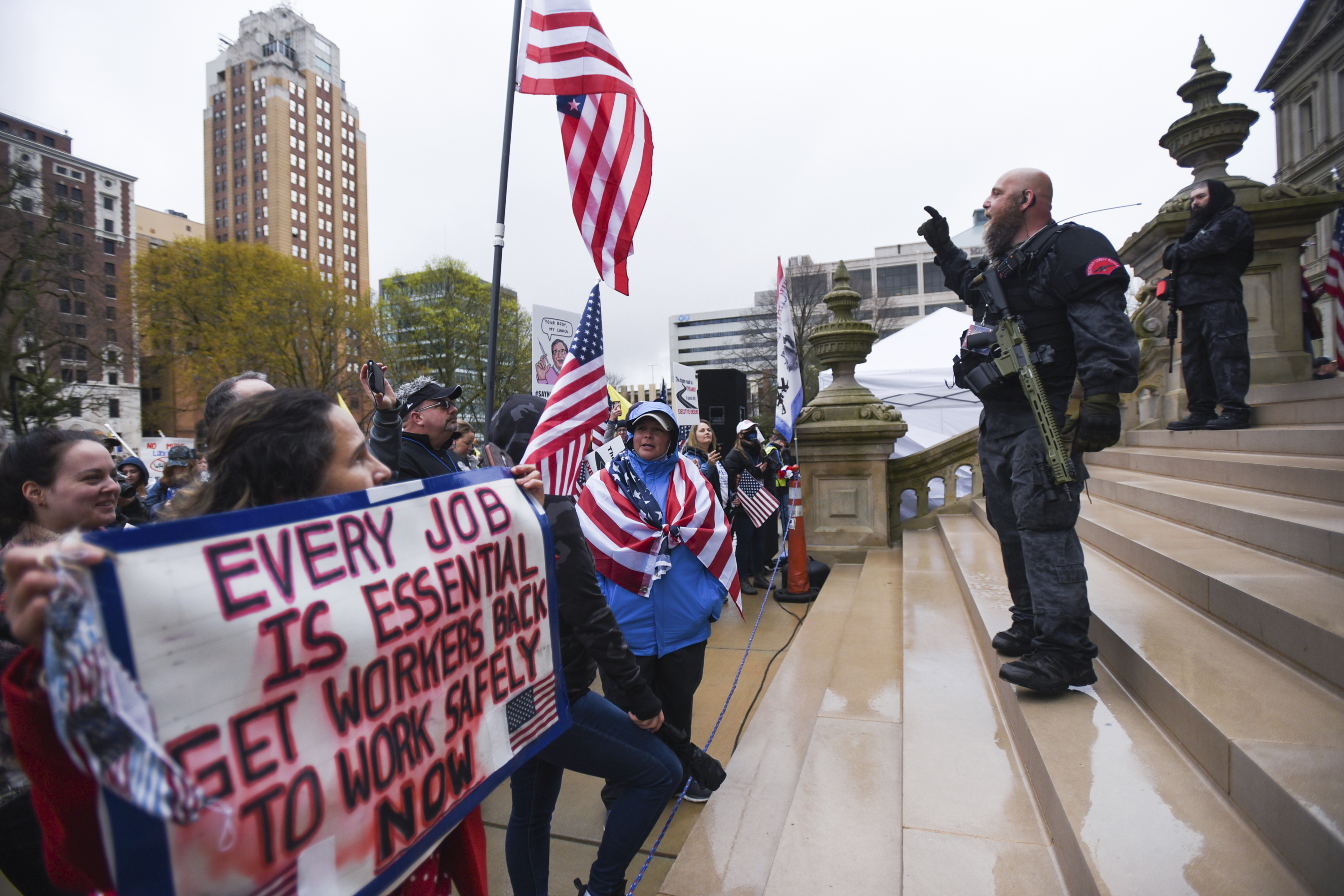 Members of the Michigan Liberty Militia, including Phil Robinson, right, join protesters at a rally at the state Capitol in Lansing, Mich., Thursday, April 30, 2020.