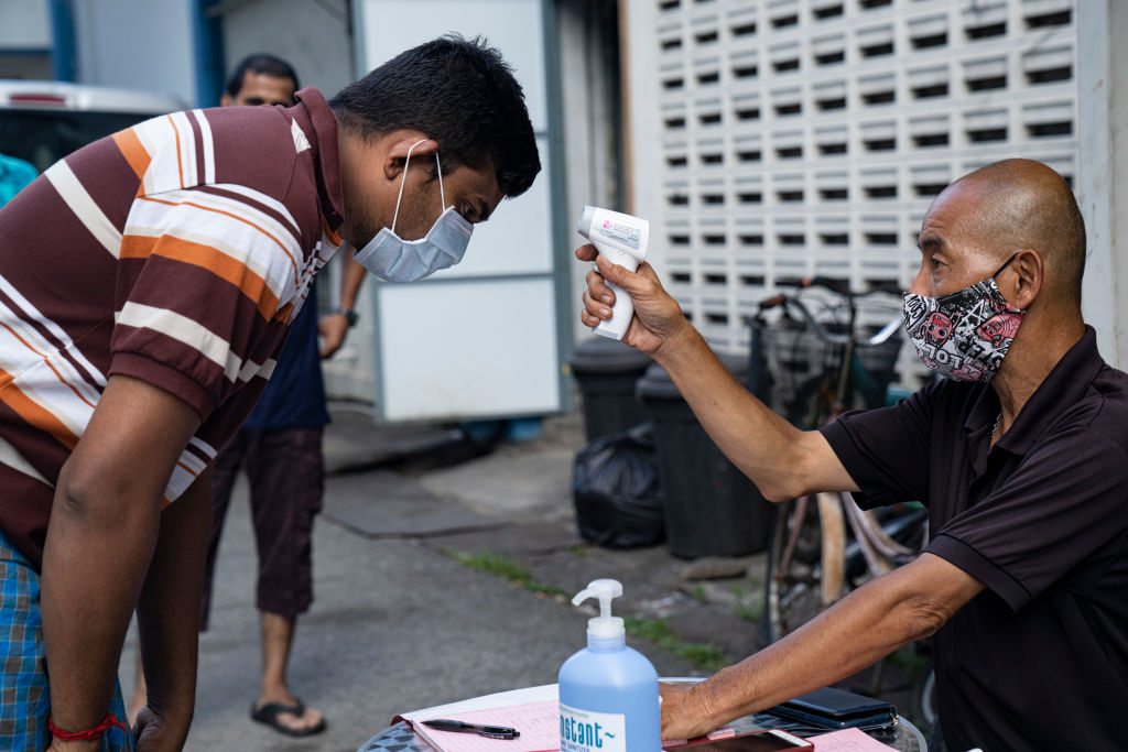A migrant worker has his temperature checked by a security guard before leaving a factory-converted dormitory in Singapore on April 17, 2020.