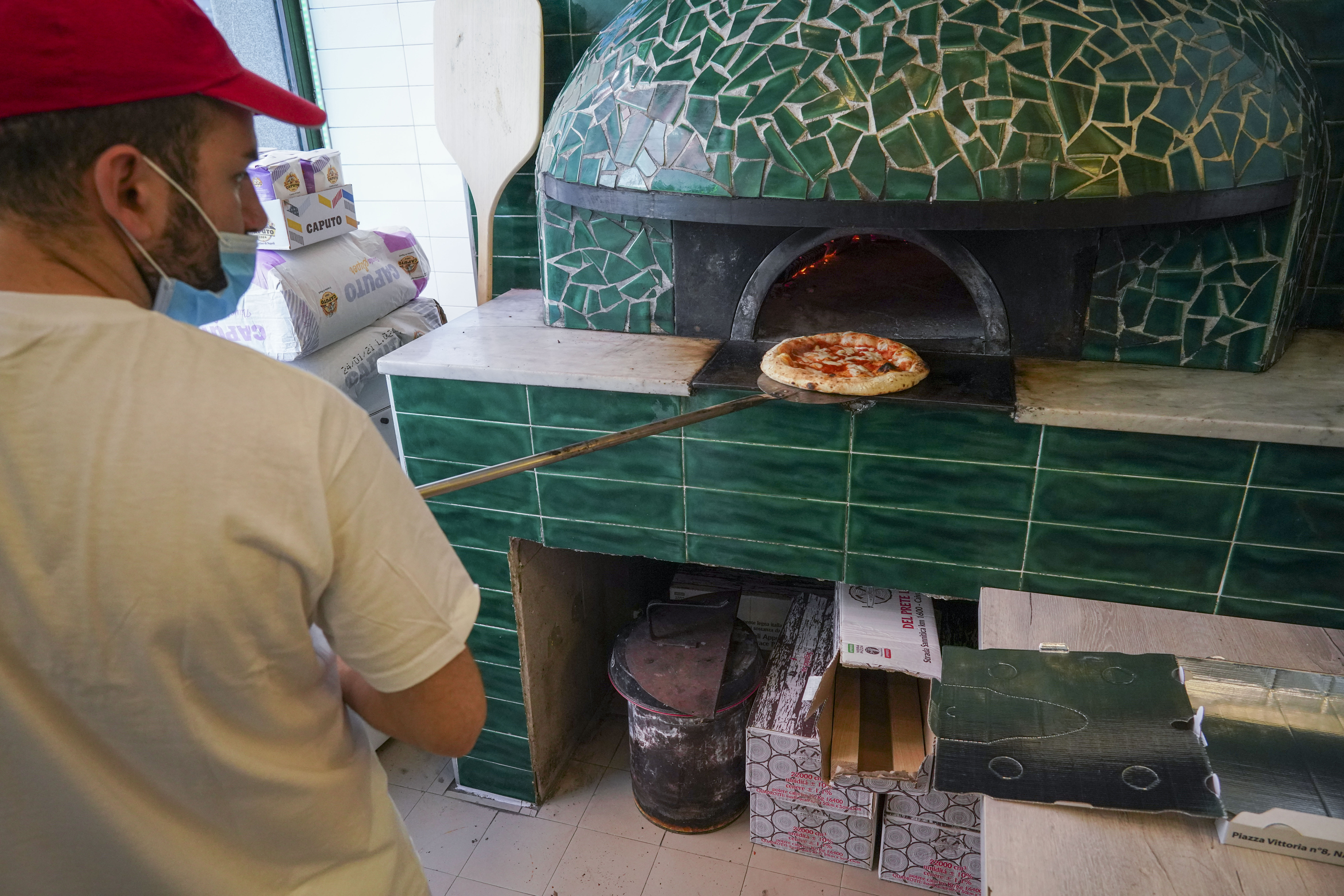 Pizzas are being prepared for home delivery at the Caputo pizzeria in Naples, Monday, April 27, 2020. Region Campania allowed cafes and pizzerias to reopen for delivery Monday, after a long precautionary closure due to the coronavirus outbreak.