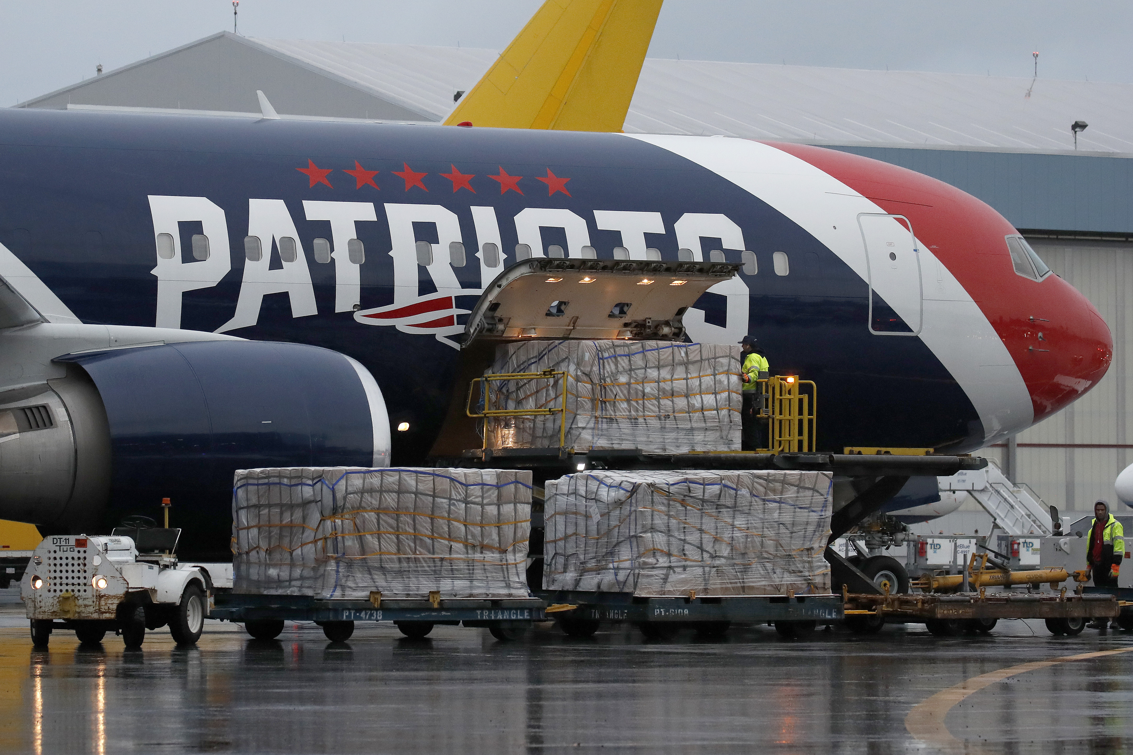 Palettes of N95 respirator masks are off-loaded from the New England Patriots football team's customized Boeing 767 jet on the tarmac, Thursday, April 2, 2020, at Logan Airport in Boston, after returning from China. The Kraft family deployed the Patriots team plane to China to fetch more than one million masks for use by front-line health care workers to prevent the spread of the coronavirus.