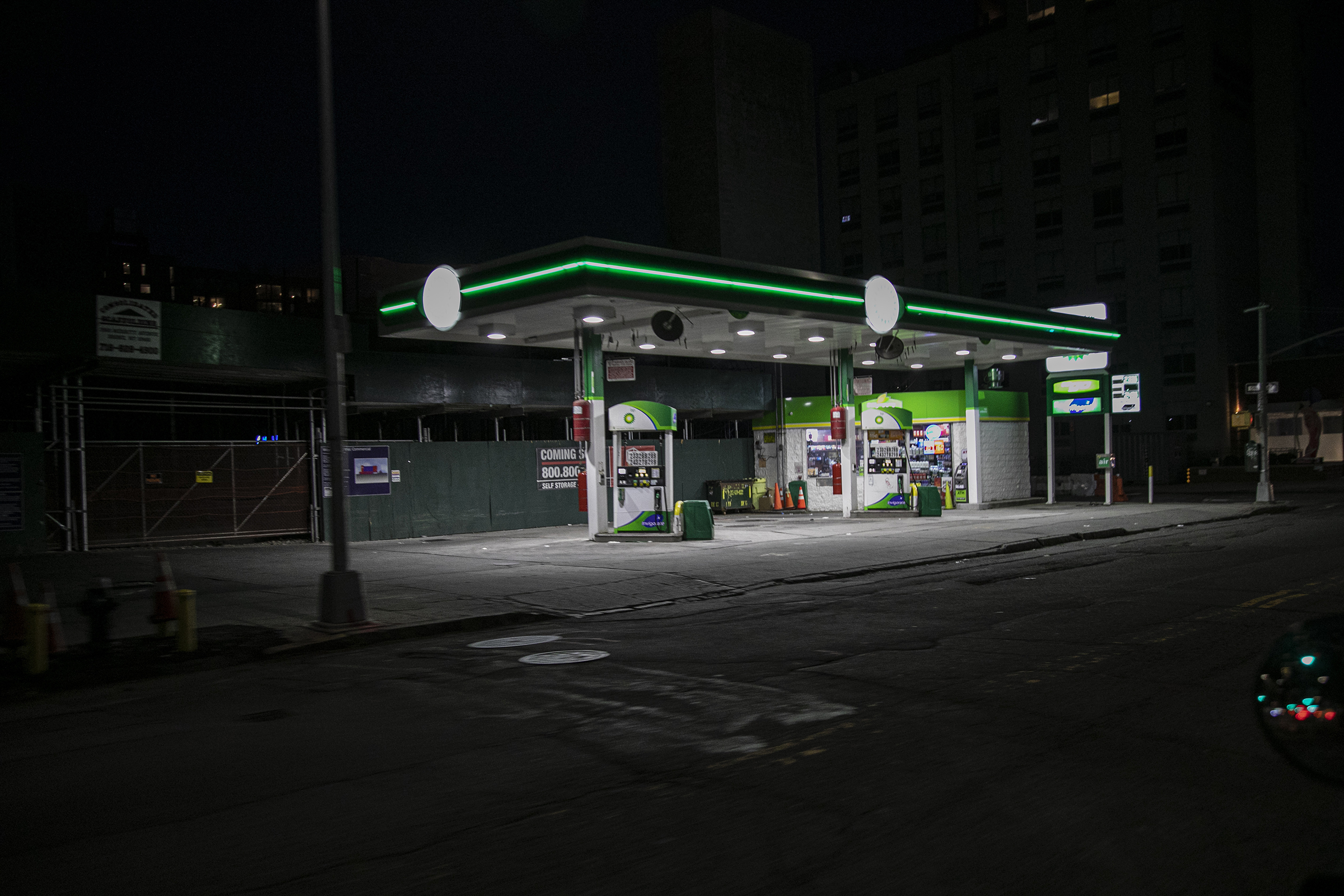 Lights illuminate a gas station on a dark and empty street in the Brooklyn borough of New York, on March 26, 2020.