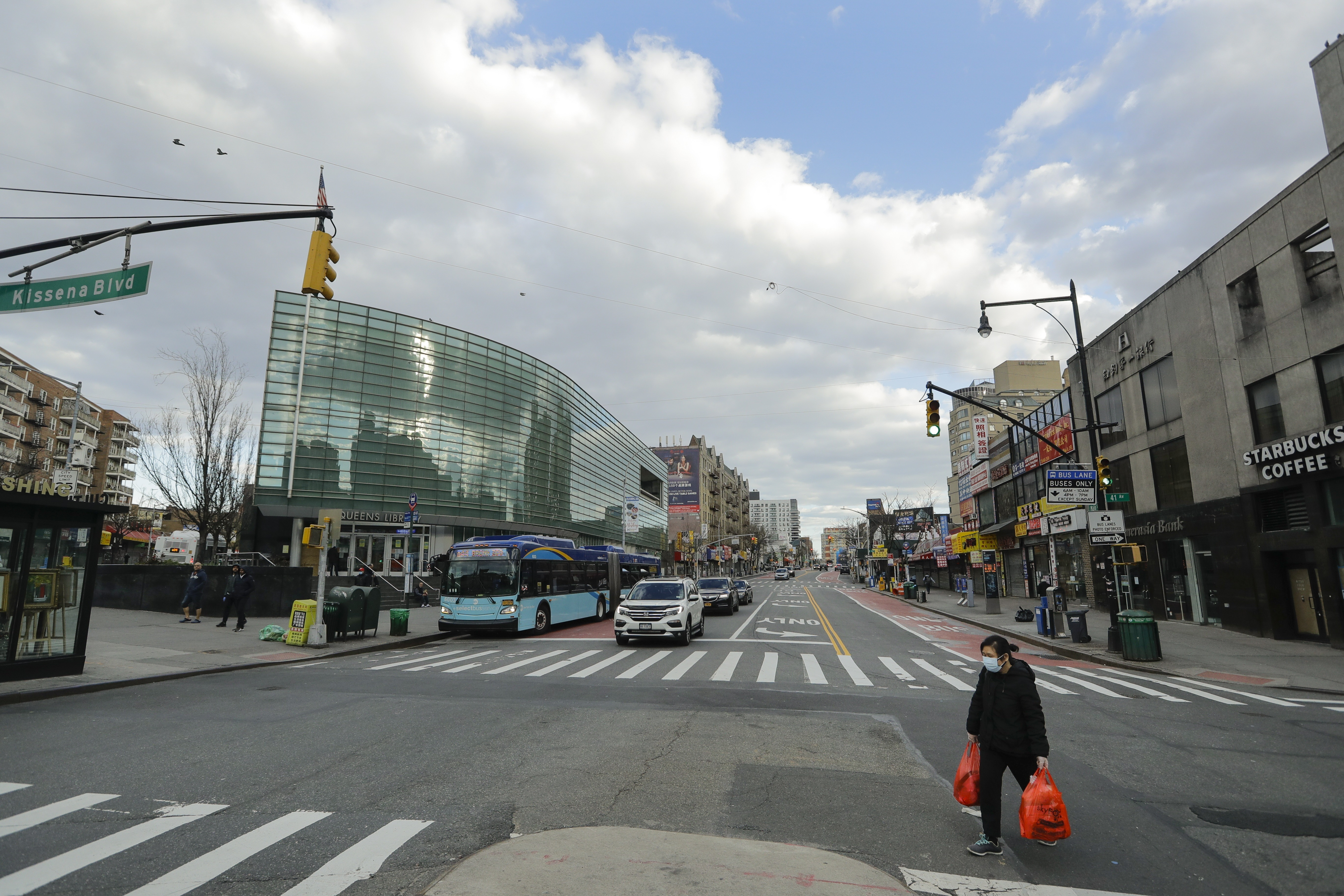 A woman wearing personal protective equipment crosses Main Street Wednesday, April 1, 2020, in the Flushing section of the Queens borough of New York.