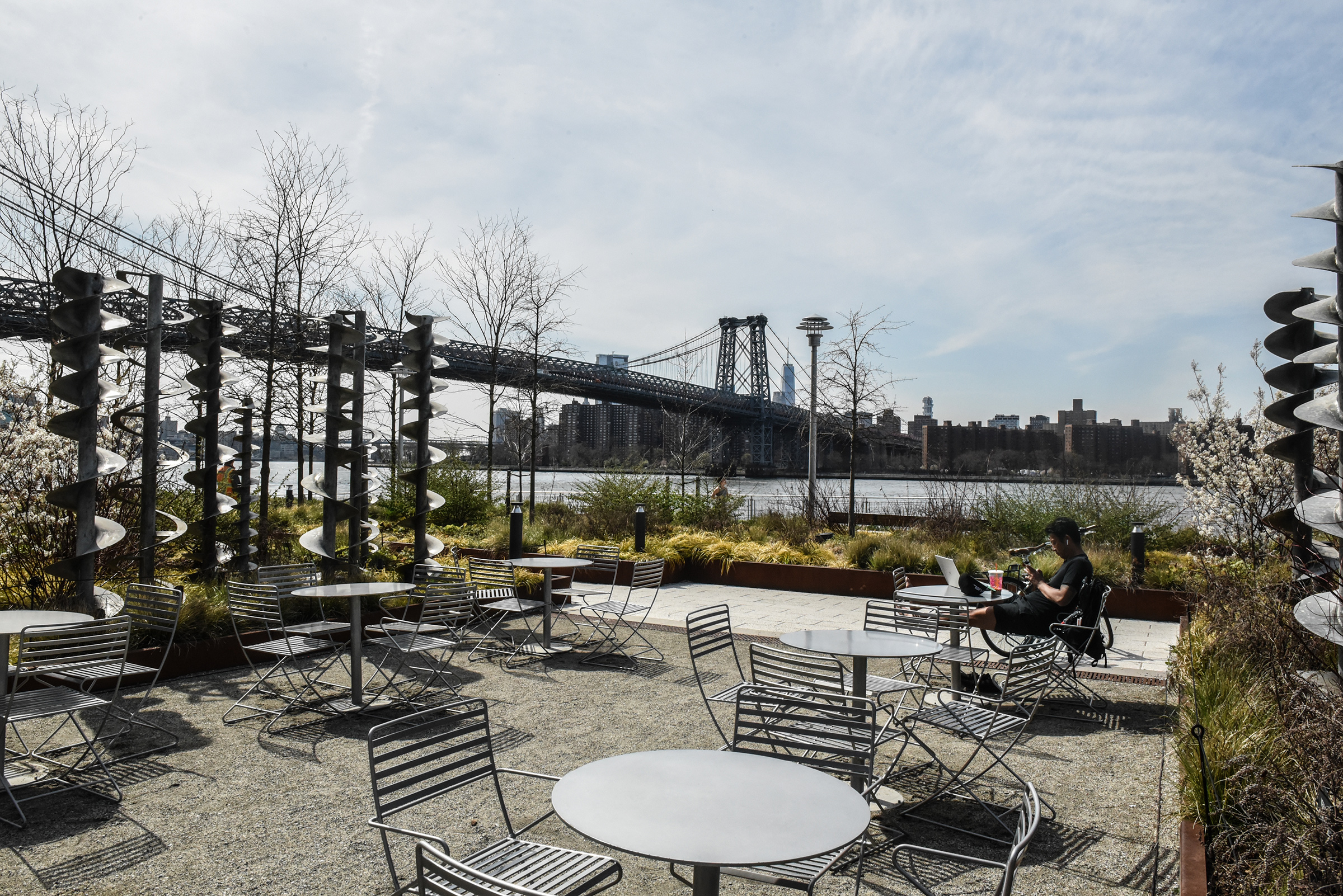 A person sits amongst empty tables and chairs at Domino Park in Williamsburg, Brooklyn on April 7