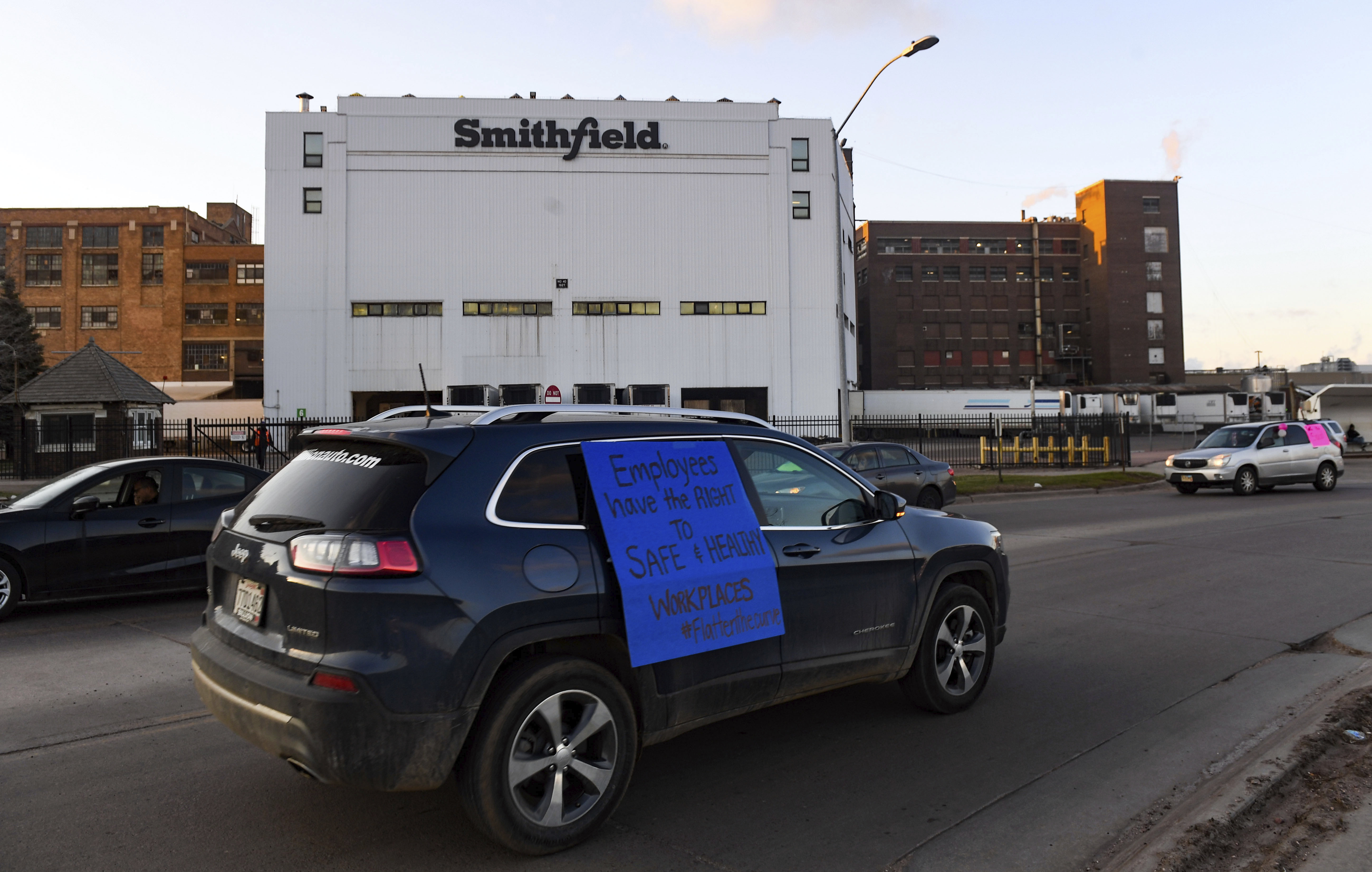 In this Thursday, April 9, 2020 photo, a car sporting a sign calling for a safe and healthy workplace drives past Smithfield Foods, Inc. in Sioux Falls. during a protest on behalf of employees after many workers complained of unsafe working conditions due to the COVID-19 outbreak. The pork processing plant in South Dakota is closing temporarily after more than 80 employees tested positive for the coronavirus.