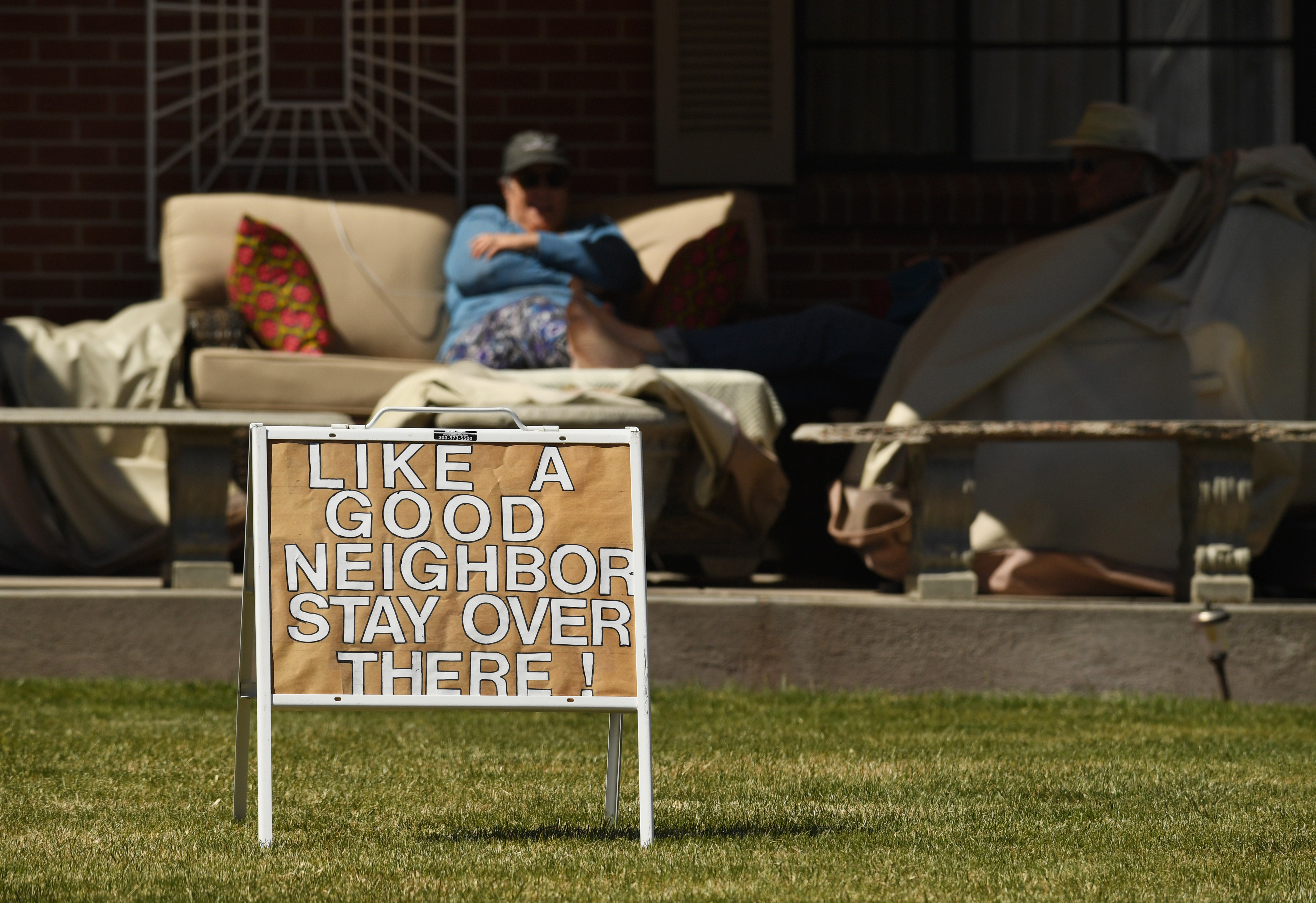 A yard sign reminds neighbors about good social distancing practices during the COVID-19 pandemic on March 31, 2020 in Lakewood, Colorado.