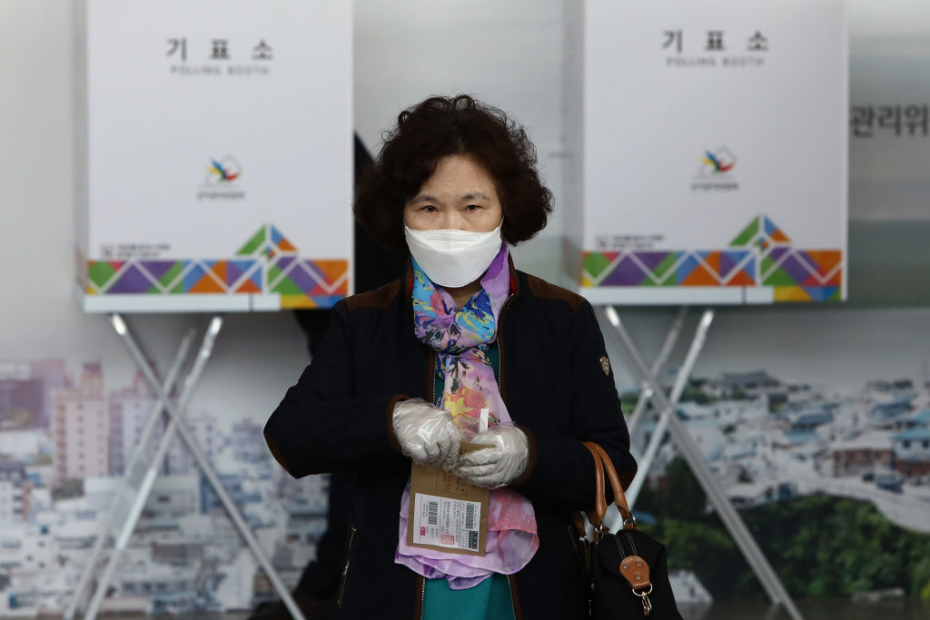 A South Korean woman wears plastic glove cast his preliminary vote for Parliamentary election in a polling station in Seoul, South Korea on April 10, 2020.