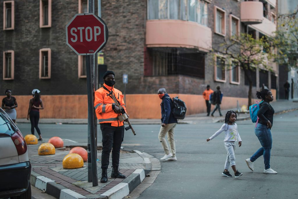Pedestrians cross a street as a private security guard stands with a semi-automatic rifle loaded with rubber bullets in Johannesburg, South Africa on April 17, 2020.