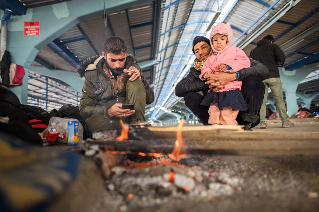 Syrian refugees sit around a campfire in an empty market hall in the Turkish border town of Edirne near the Pazarkule-Kastanies border crossing on March, 5 2020.