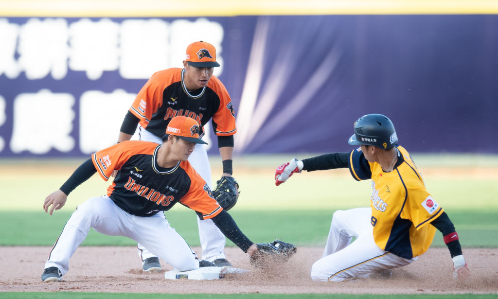 Infielder Wei Chen Wang (R) #9 of CTBC Brothers is tagged out during the CPBL game between CTBC Brothers and Uni-President Lions at Taichung Intercontinental Baseball Stadium on April 12, 2020 in Taichung, Taiwan. Taiwan's Chinese Professional Baseball League started April 11 2020. Due to COVID-19, only staff and members of the media were allowed to attend.